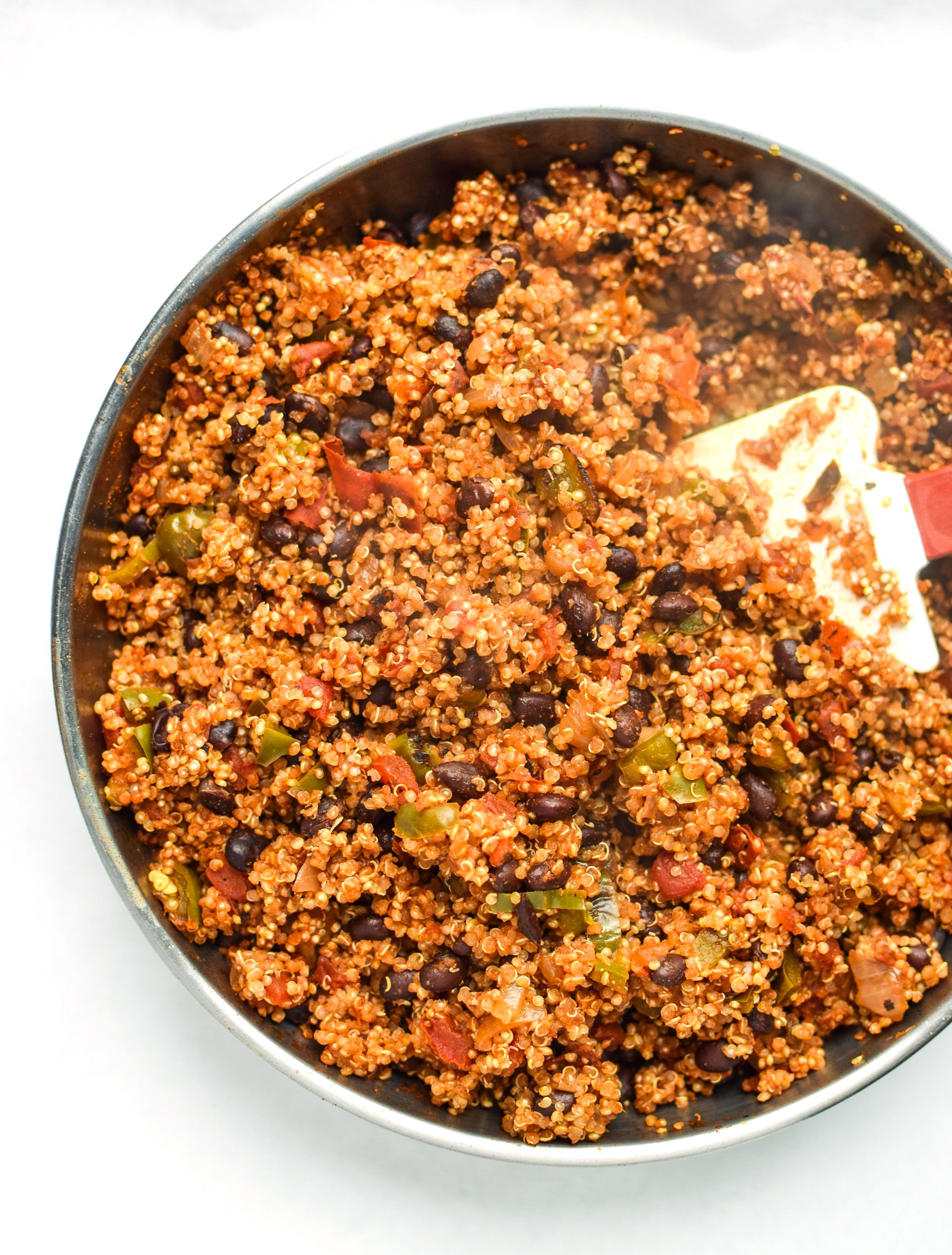 An overhead view of a skillet of cooked mexican quinoa with fire roasted tomatoes, peppers and onions.