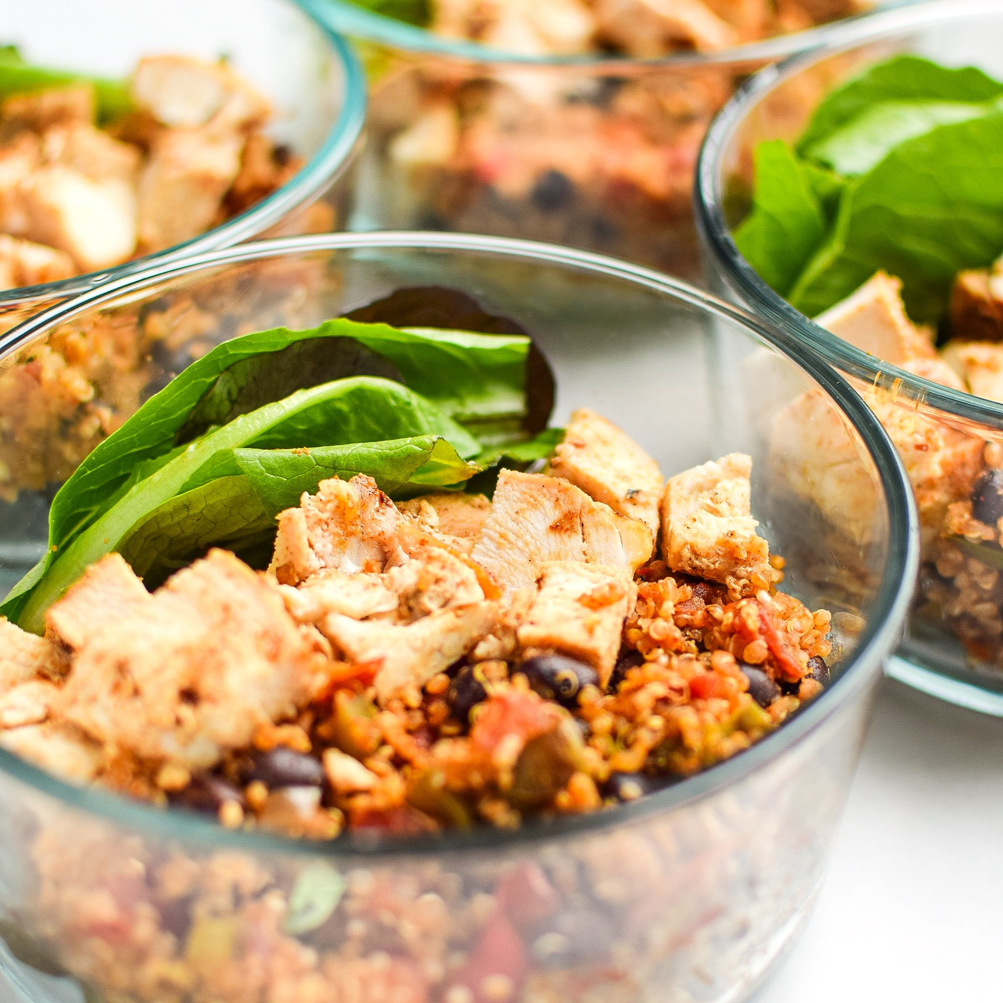 Meal prep lunch with mexican quinoa, chicken breast and hearty green leaves in Pyrex.