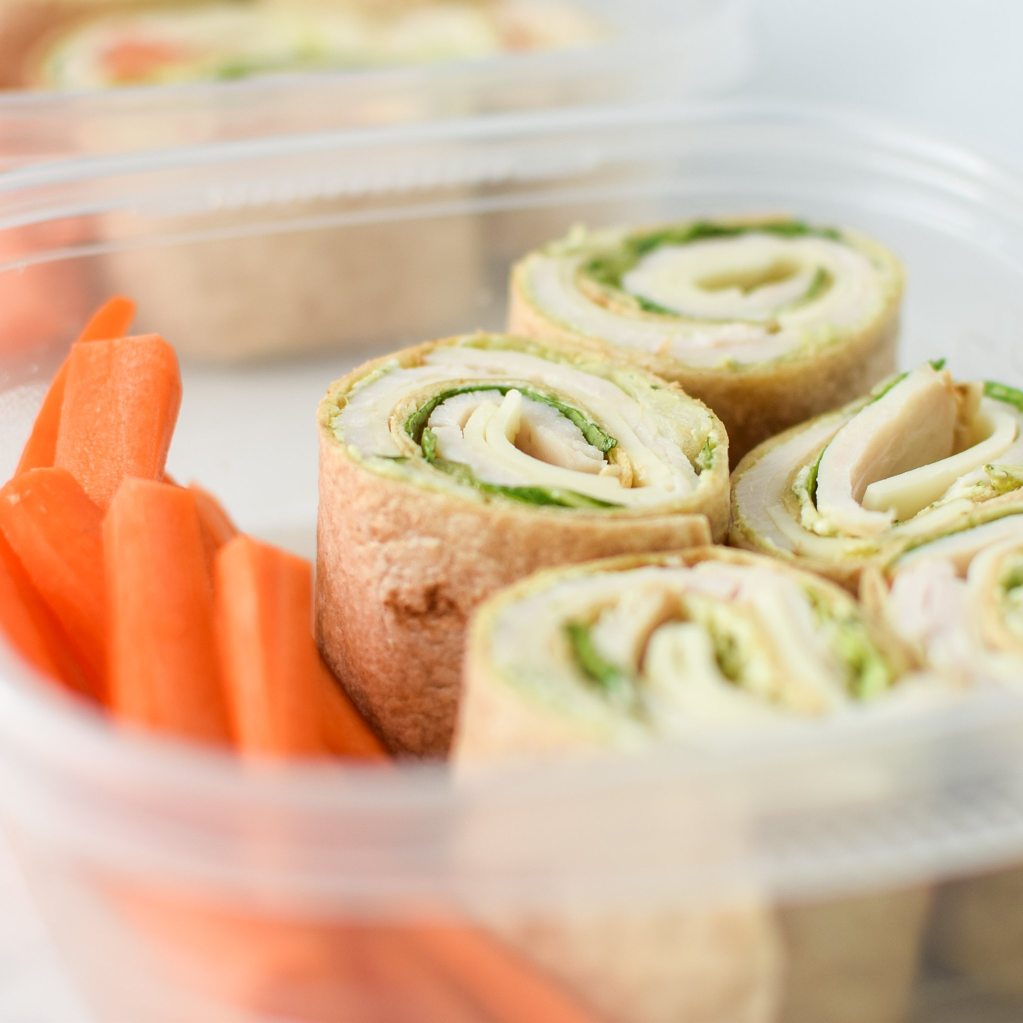 Turkey Pesto Tortilla Pinwheels meal prepped with carrot sticks