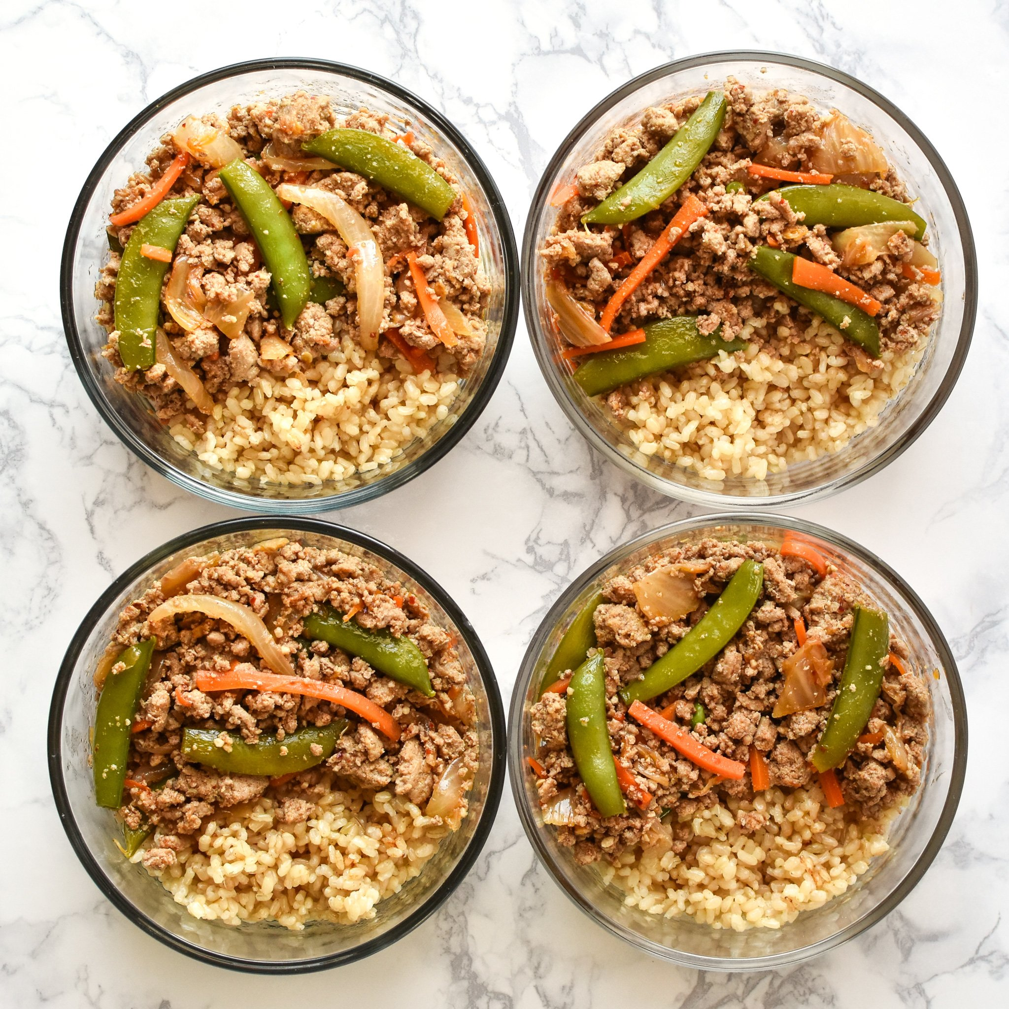 Ground turkey snap pea rice bowl meal prep in round pyrex meal prep containers.