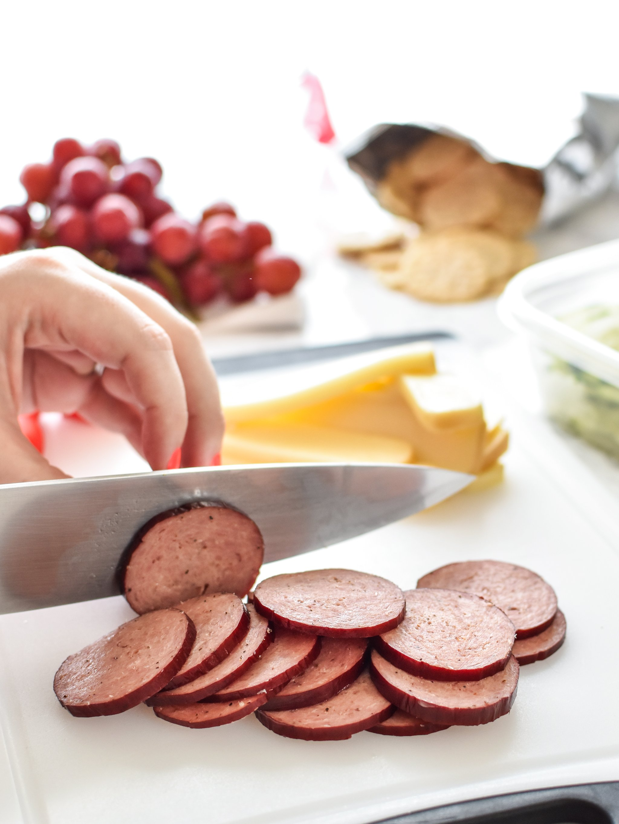 How to Turn Cheese and Crackers into DIY Adult Lunchables - Cutting up some turkey summer sausage for my adult lunchables.