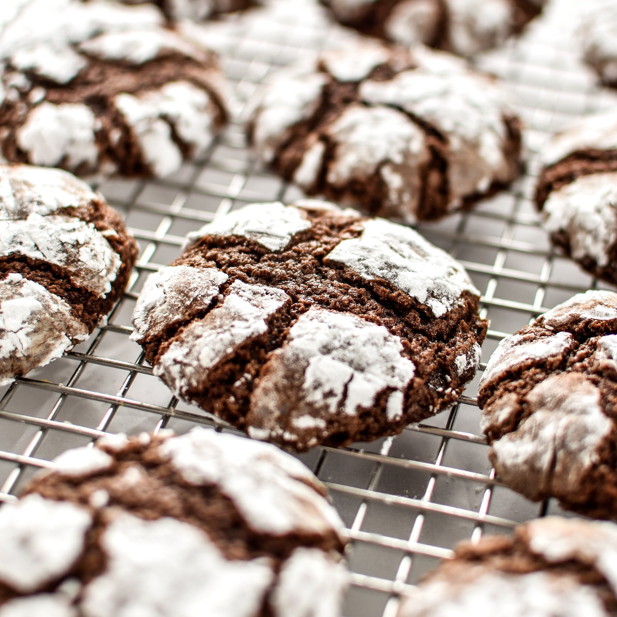 Classic Chewy Chocolate Crinkle Cookies on a cooling rack.
