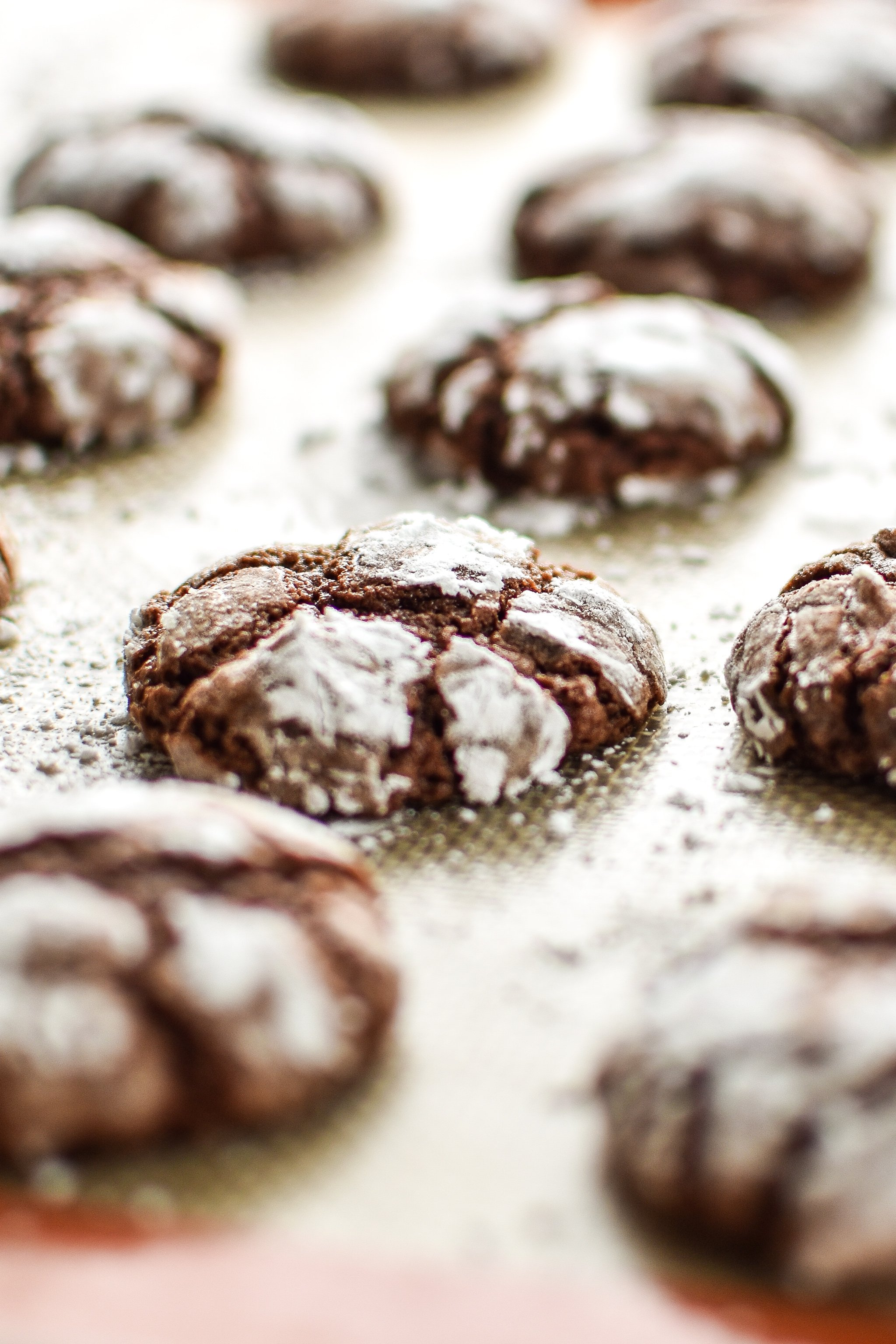 Classic Chewy Chocolate Crinkle Cookies on a silpat baking pan.