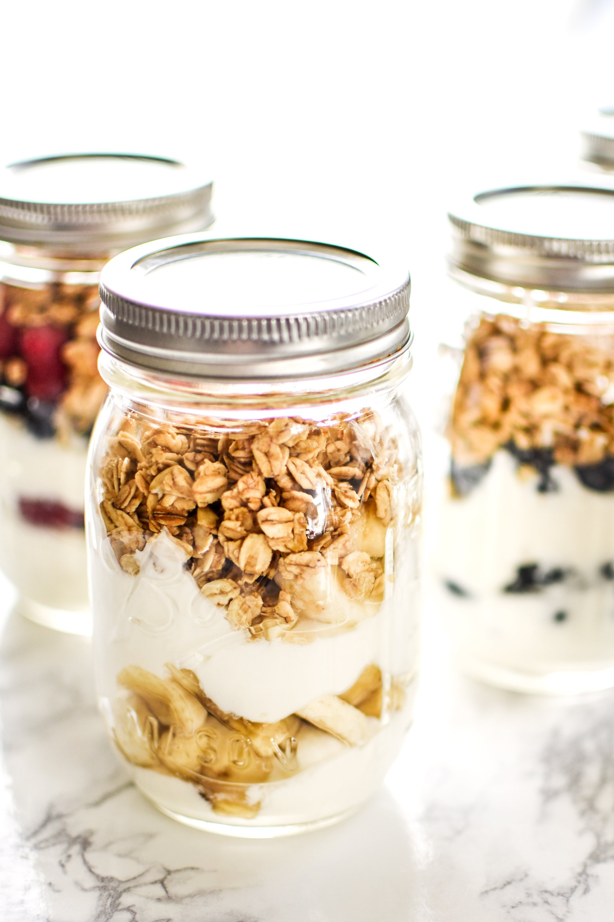 Mason jar green yogurt parfaits with granola and fruit.