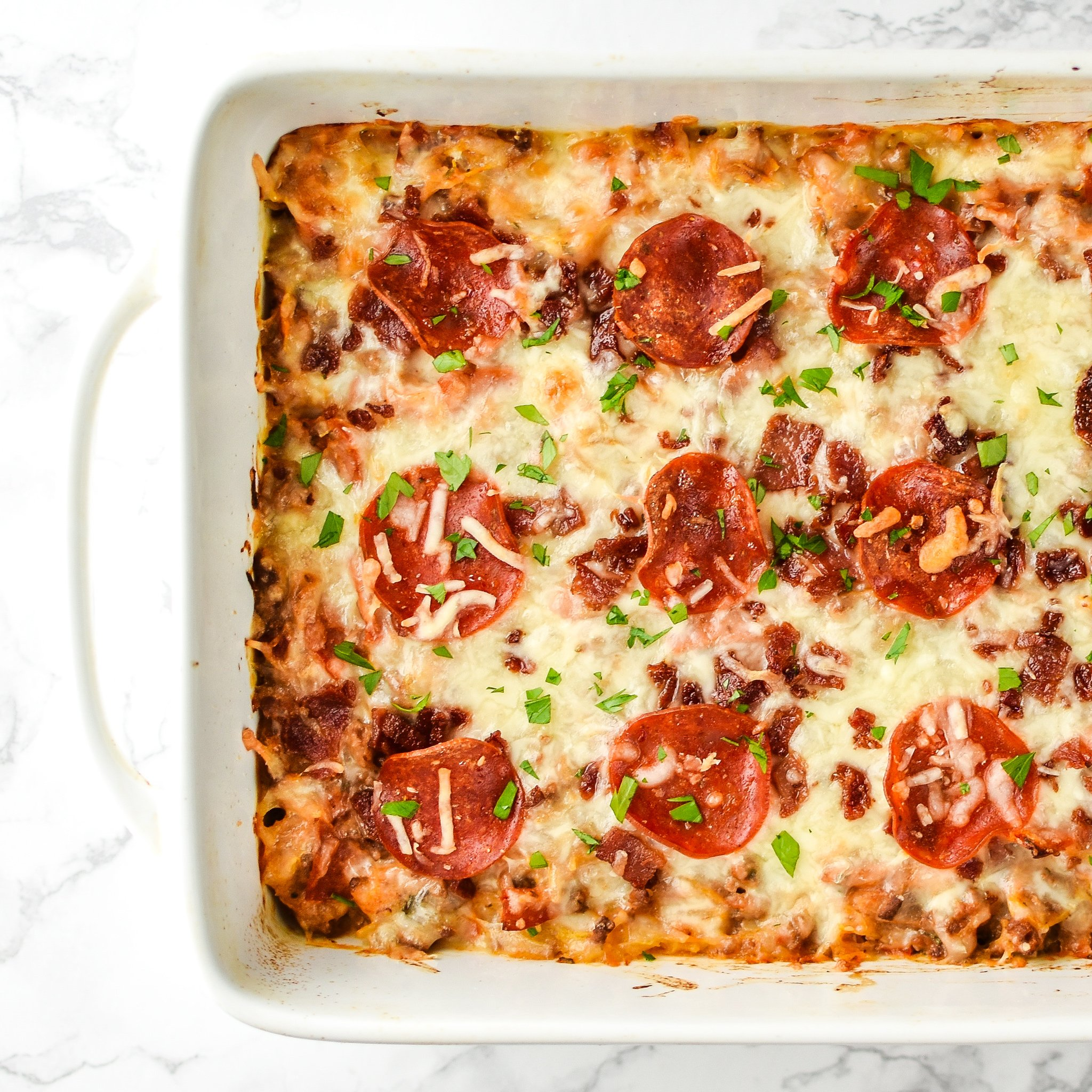 Mouth-watering top view of Meat Lover's Spaghetti Squash Pizza Casserole - It's pizza, but morphed into a not-that-bad-for-you spaghetti squash casserole with meat lover's toppings! - ProjectMealPlan.com