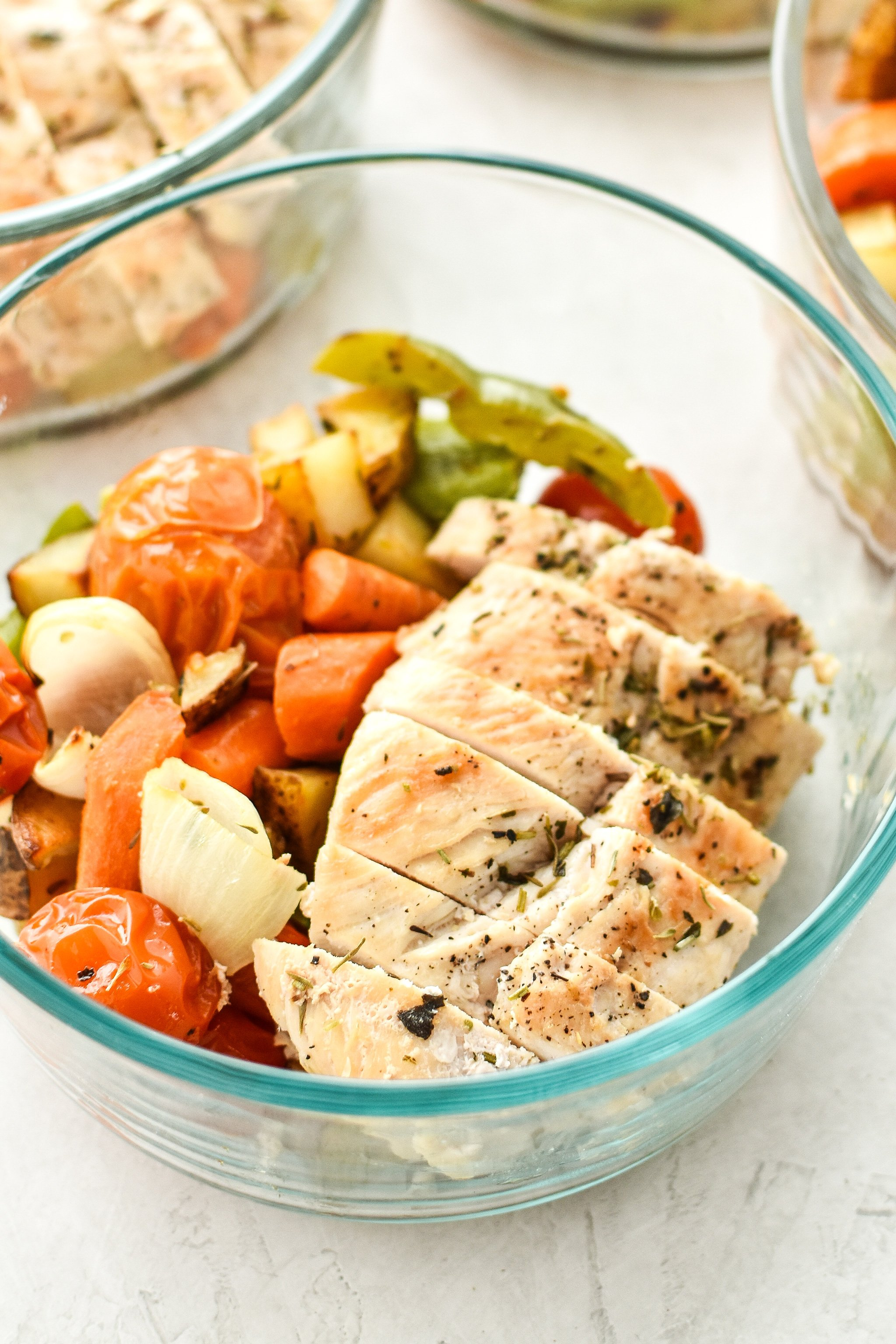 Simple, healthy, Meal Prep Italian Seasoned Chicken with Roasted Imperfect Vegetables including potatoes, cherry tomatoes, onions, and bell peppers!