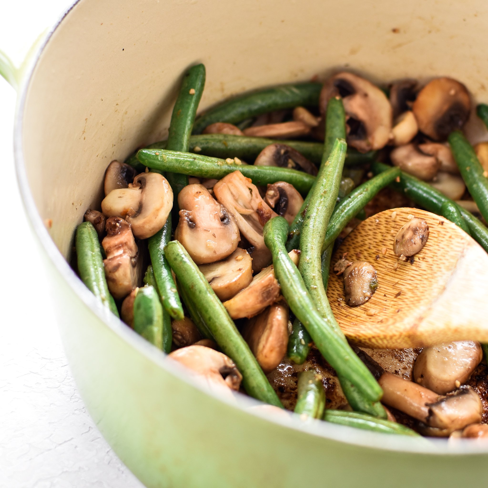 Mushrooms and green beans cooking the Dutch Oven. This One-Pot Pesto Chicken and Rice is the perfect idea if you're short on dinner prep time. - ProjectMealPlan.com