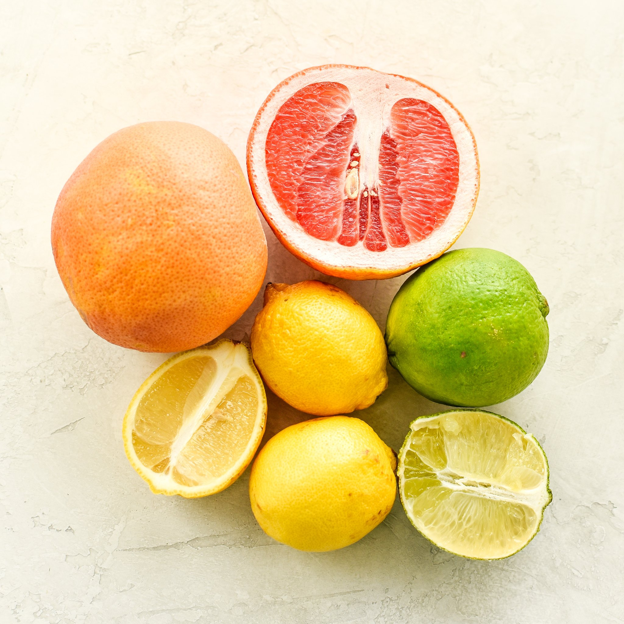 Citrus fruits laid out on a counter viewed from above - including grapefruit, lemons and limes. Some are cut in half.