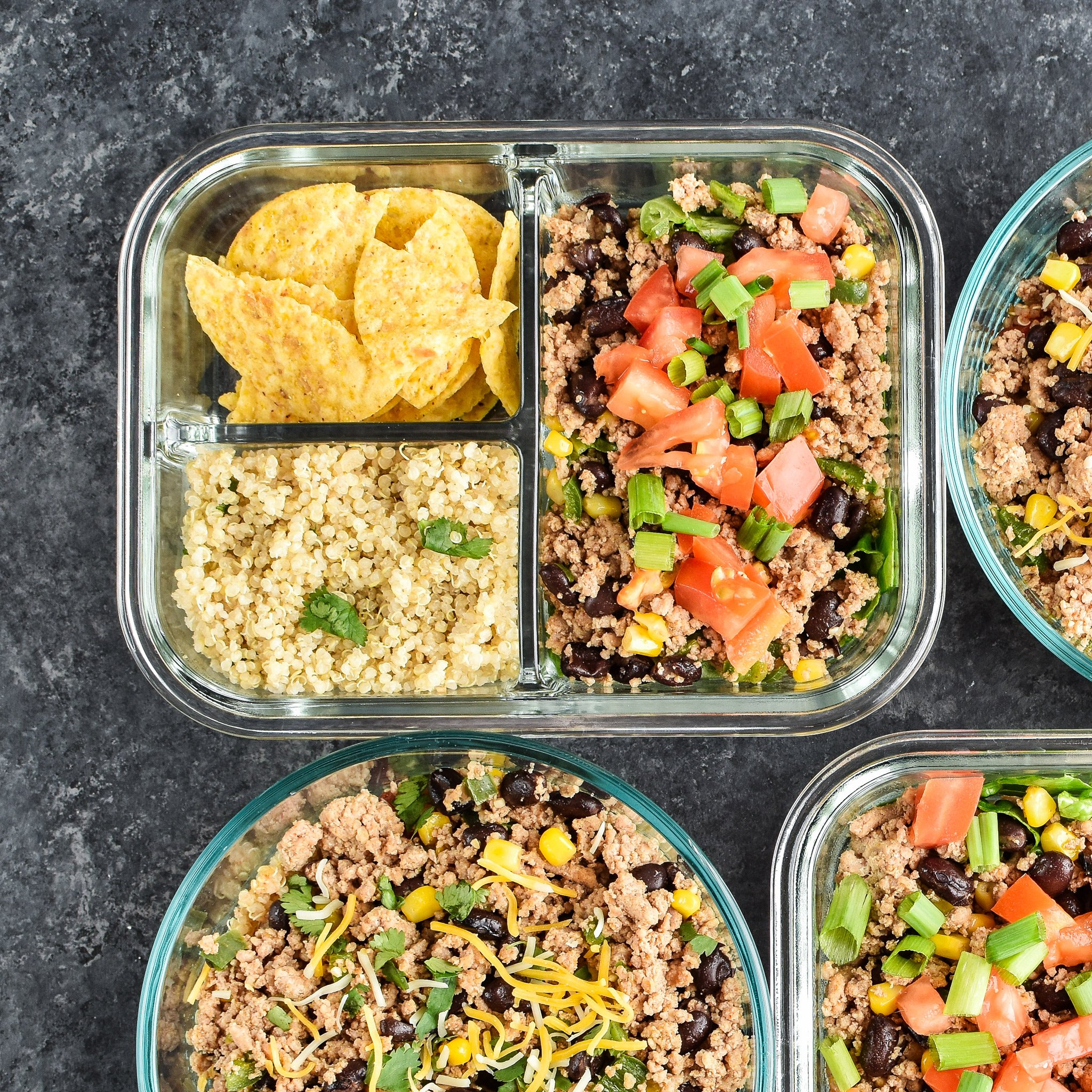 Meal prepped lunches viewed from above for Hot & Cold Turkey Taco Meal Prep; two taco salads with quinoa and chips on the side and two taco bowls with tomato and green chili quinoa.