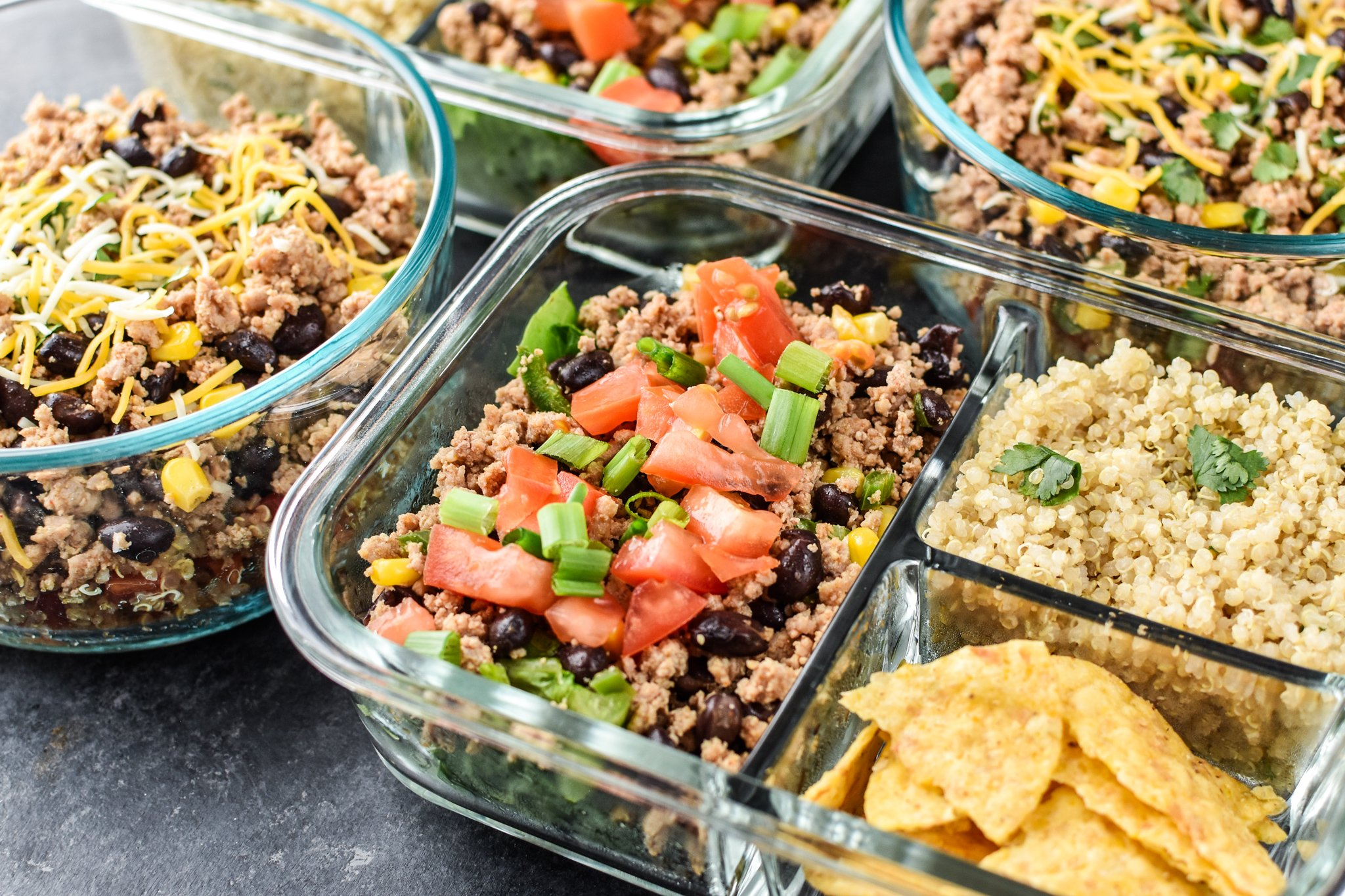 Four meal prepped lunches viewed from above for Hot & Cold Turkey Taco Meal Prep; two taco salads with quinoa and chips on the side and two taco bowls with tomato and green chili quinoa.