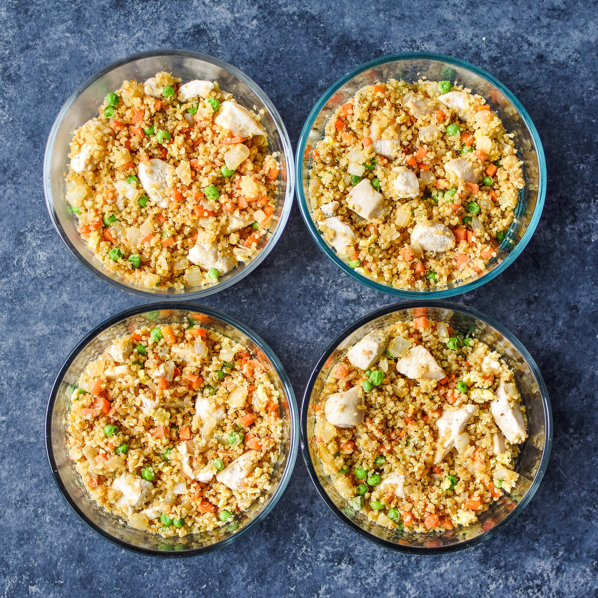 Chicken quinoa fried rice portioned into meal prep bowls.