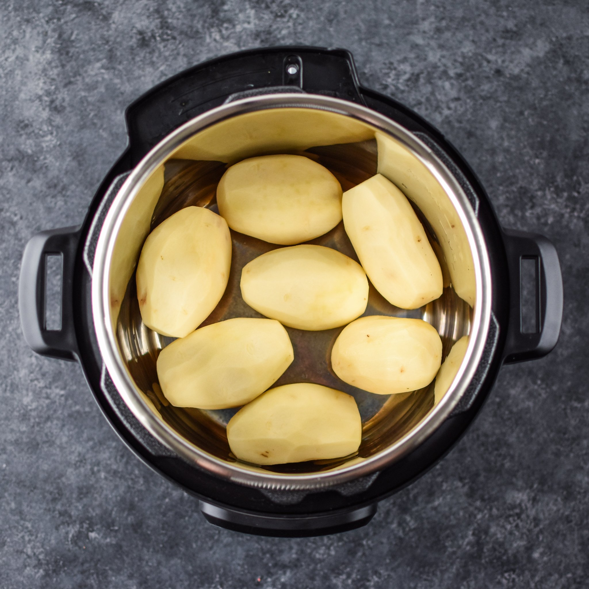 7 russet potatoes peeled in an Instant Pot ready to be cooked.