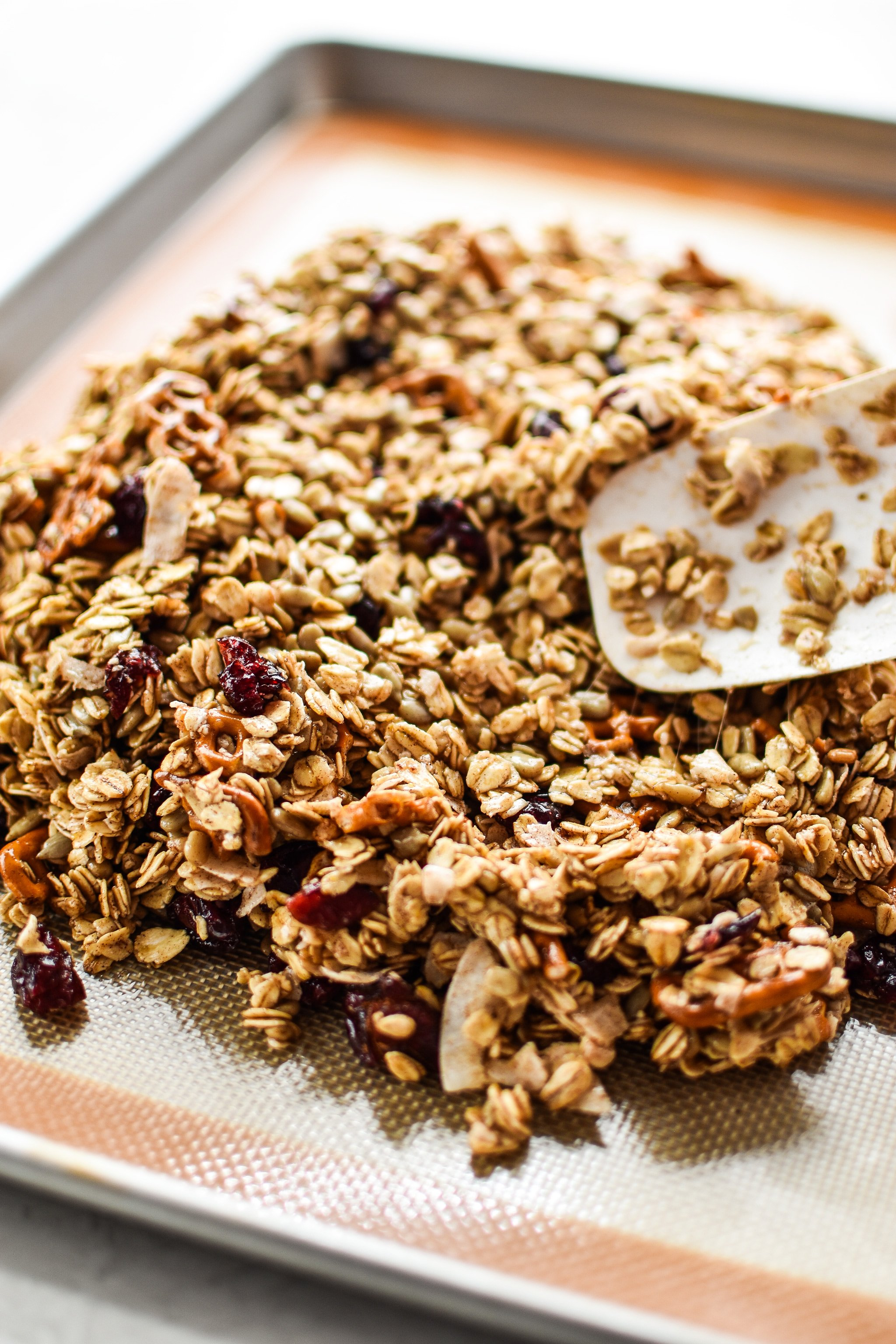 Using a spatula to spread the granola mixture on the sheet tray.