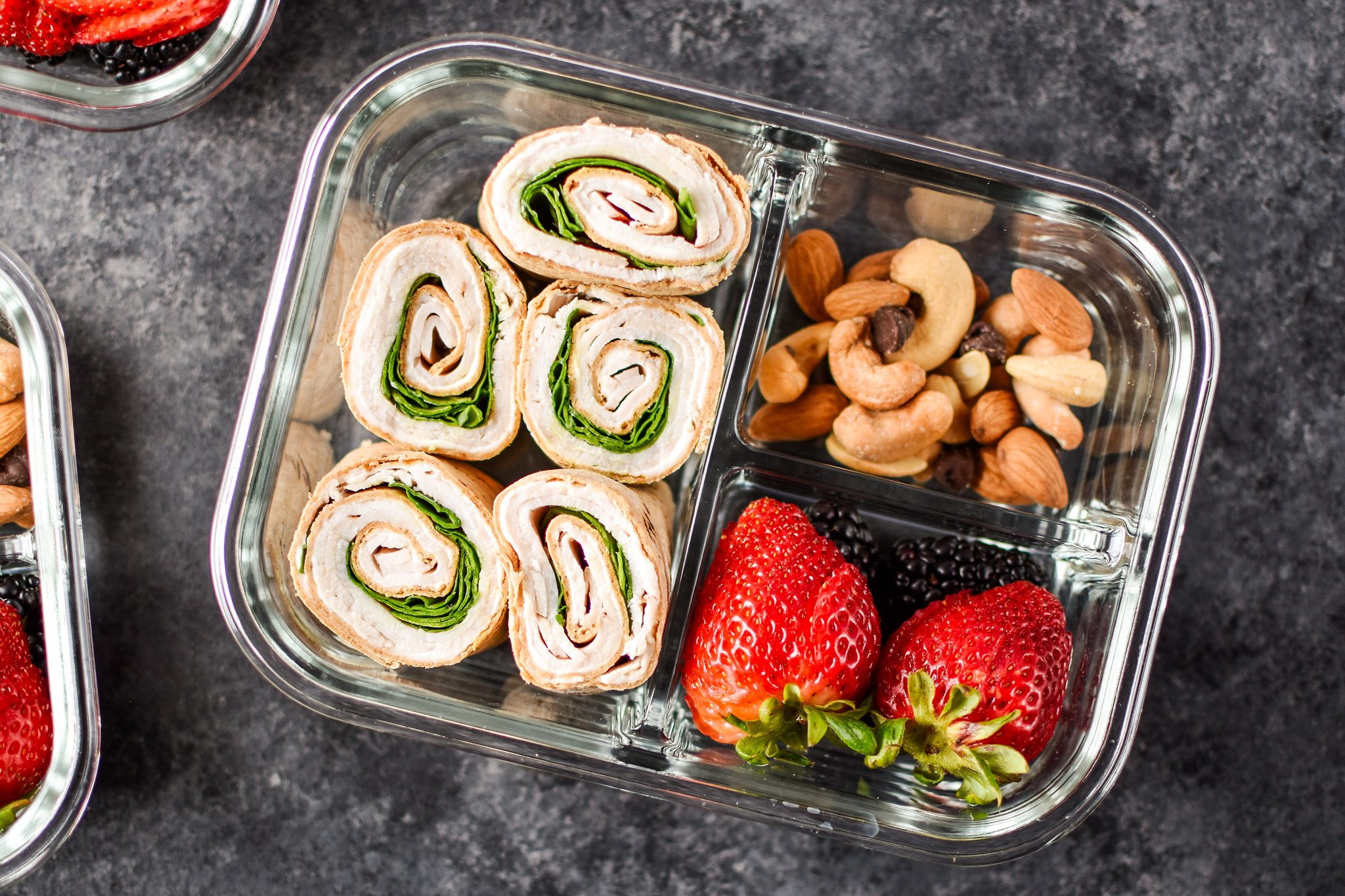 A turkey pinwheel meal prep with berries and nuts.
