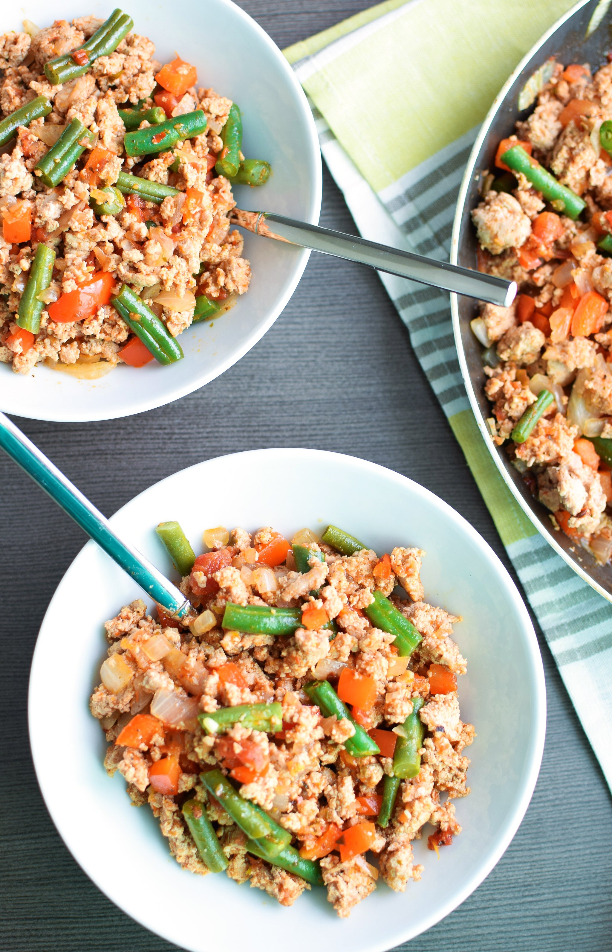 Servings of the Green Bean Turkey Skillet portioned into bowls from the skillet.