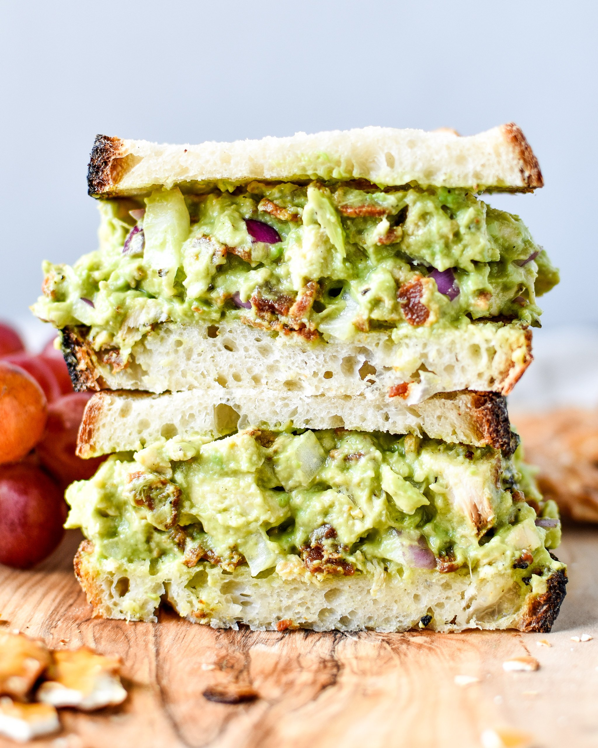 Two halves of chicken bacon avocado salad sandwich stacked on top of each other.