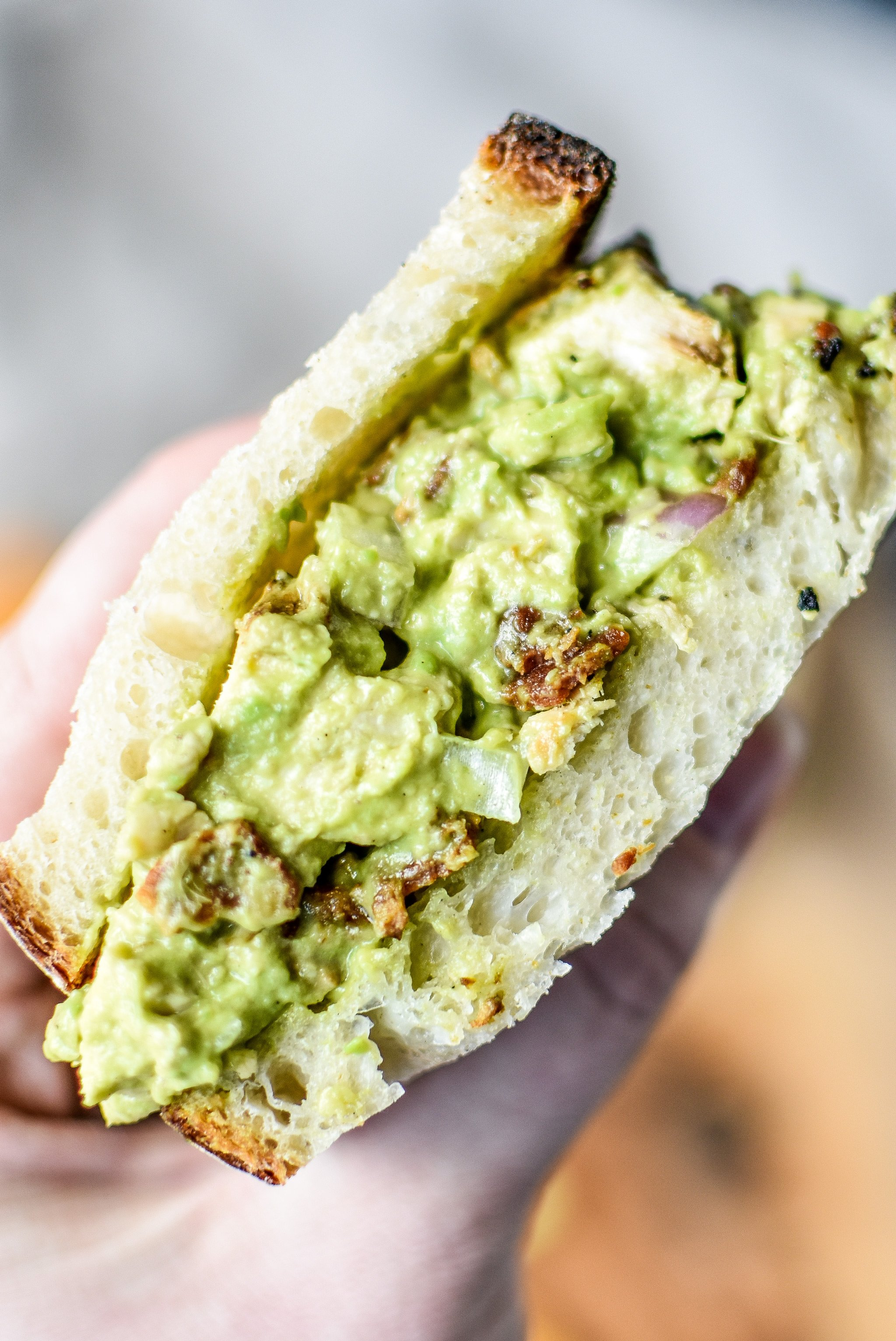 Holding a half of the delicious chicken bacon avocado salad sandwich.