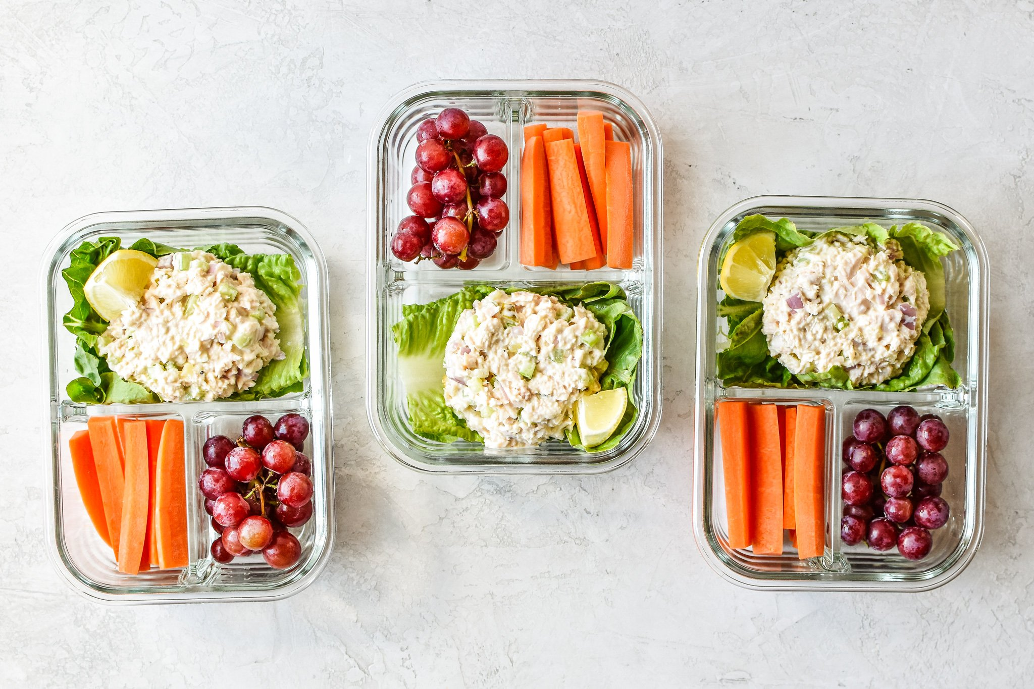 Three tuna salad lettuce wraps meal prep lunches on the counter viewed from above.