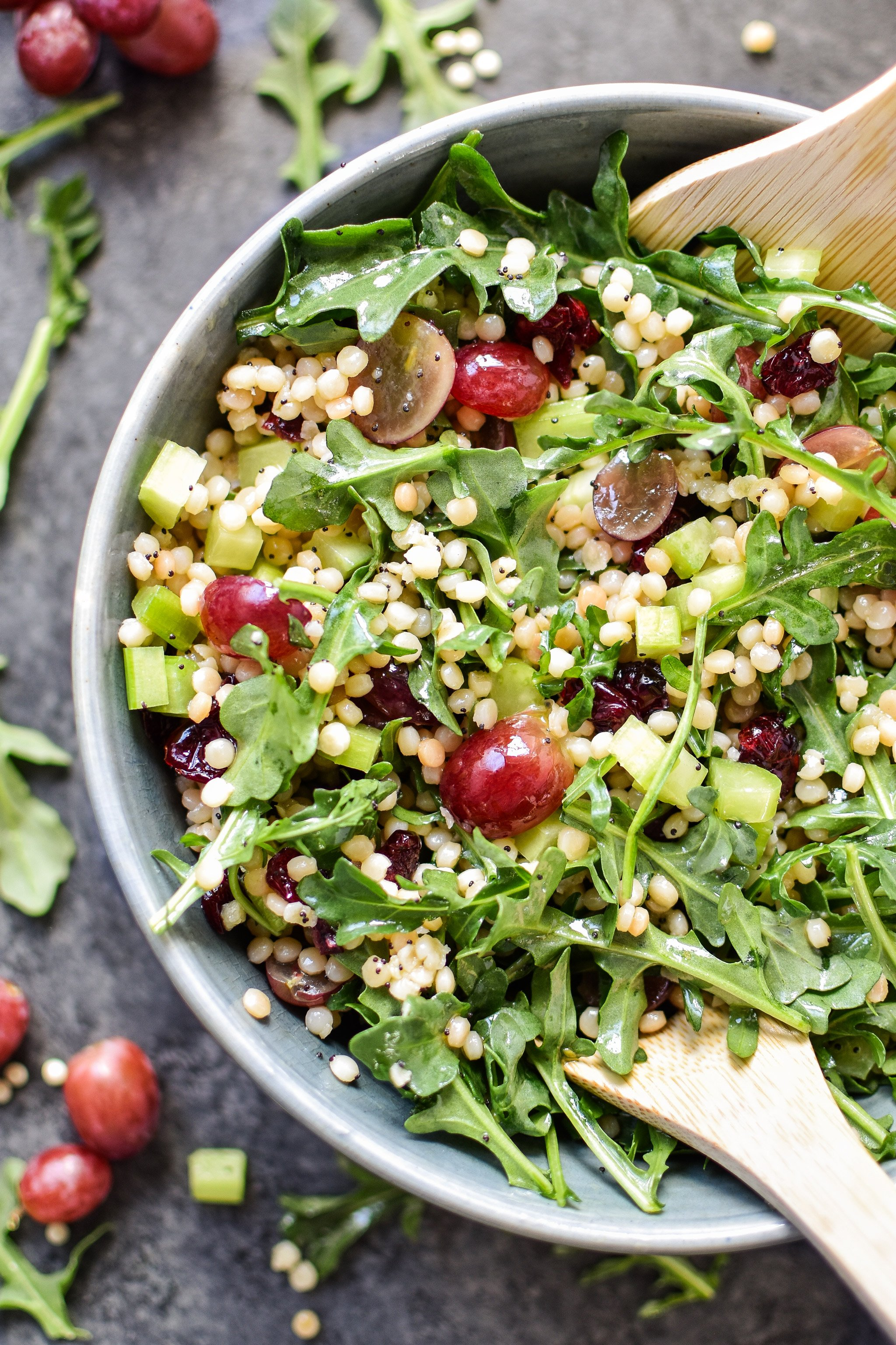 Make-Ahead Lemon Poppyseed Couscous Arugula Salad viewed from above in a serving bowl with utensils.