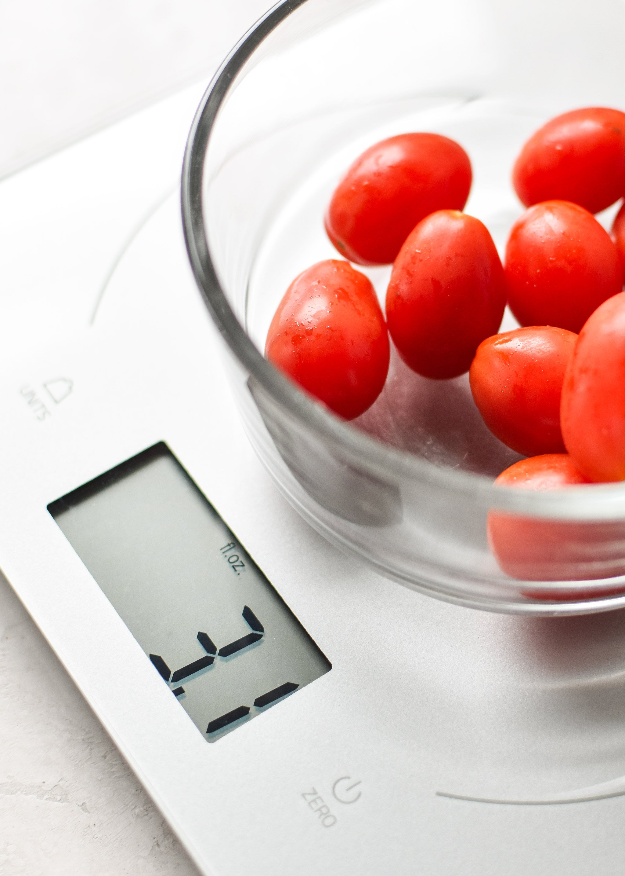 Portioning grape tomatoes for meal prep using a kitchen scale.