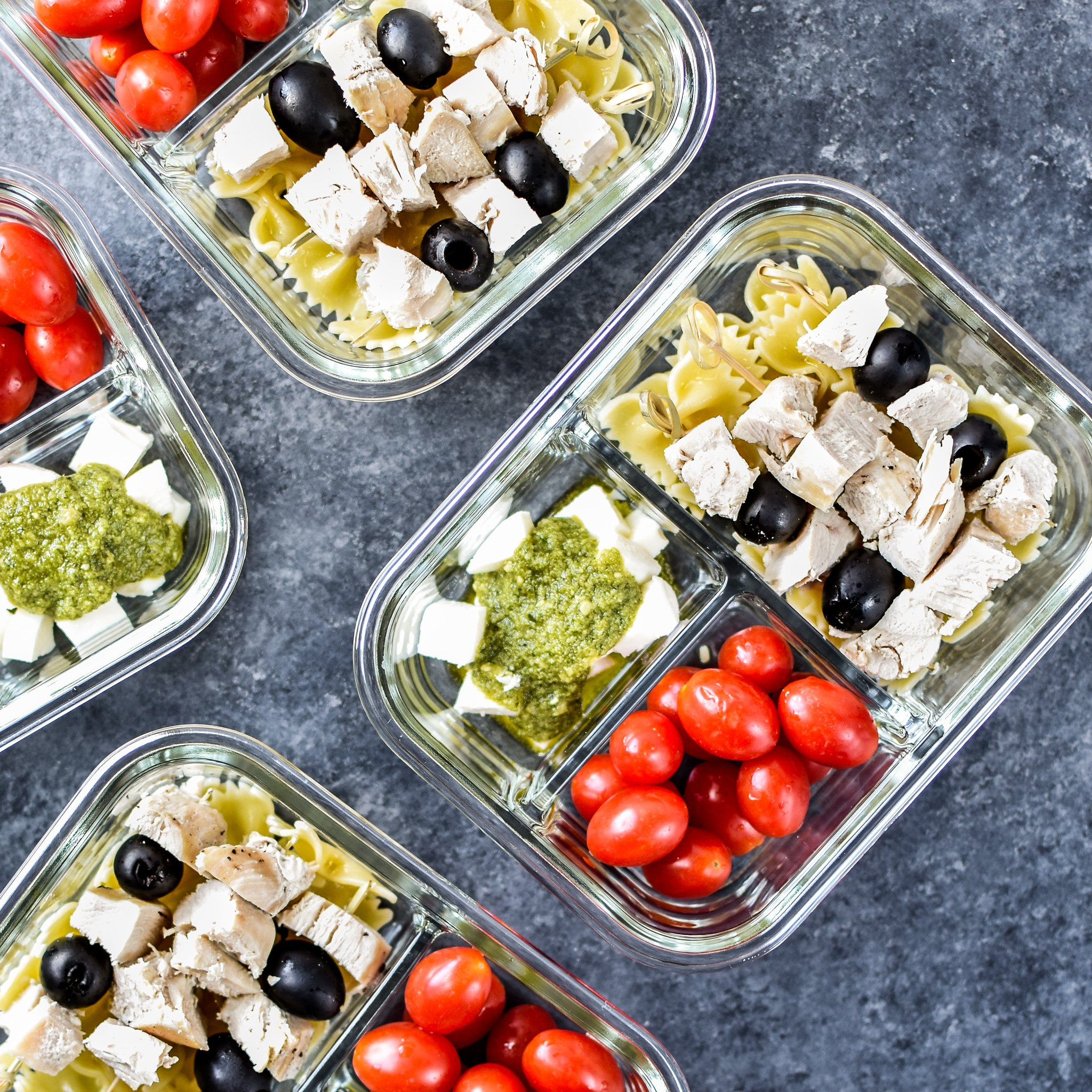 A view of the DIY Chicken Pesto Pasta Skewers Meal Prep from above, including grape tomatoes, fresh mozzarella and traditional pesto!