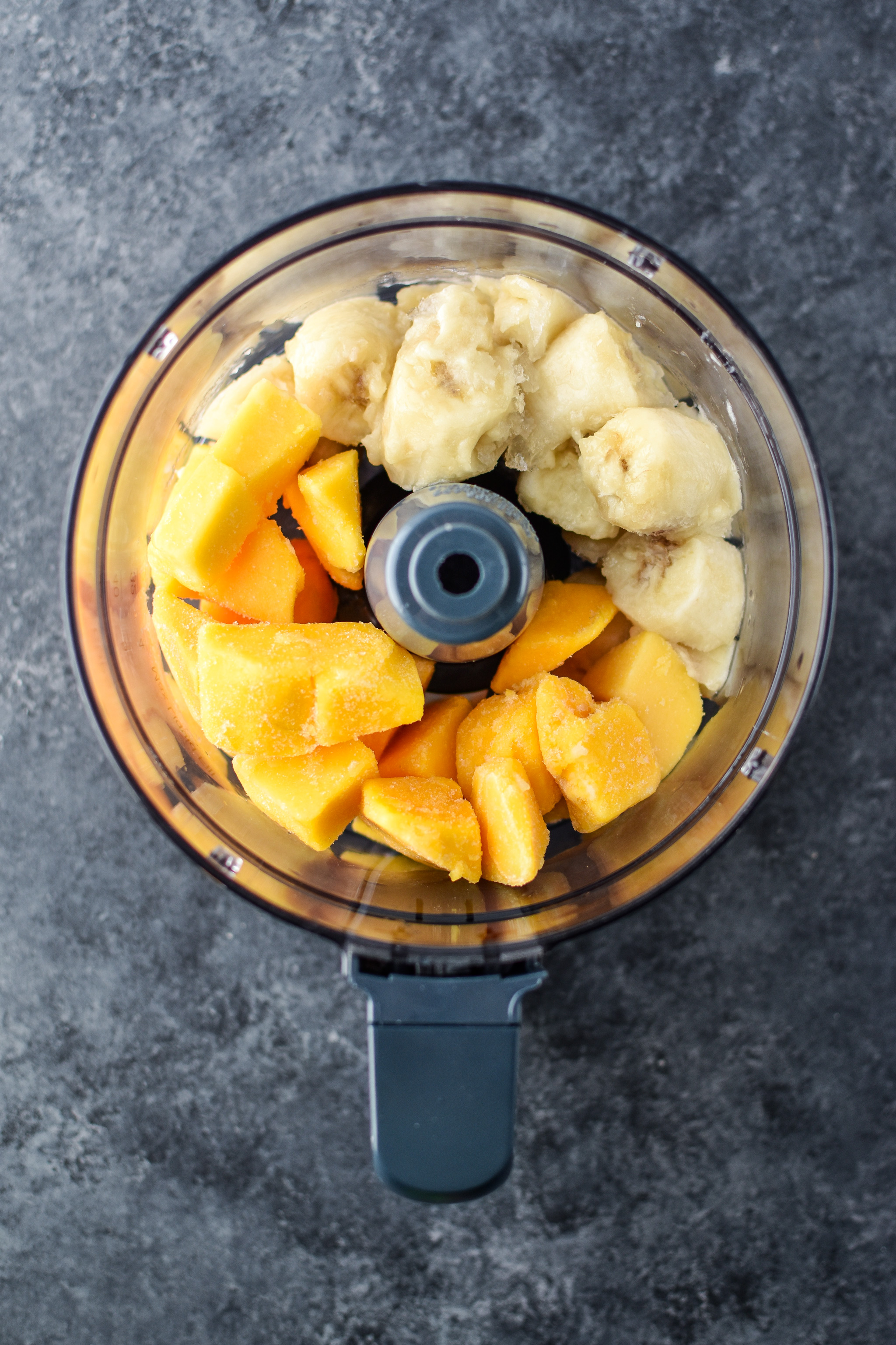 Above view of the ingredients in the food processor to make Mango Lime Nice Cream.