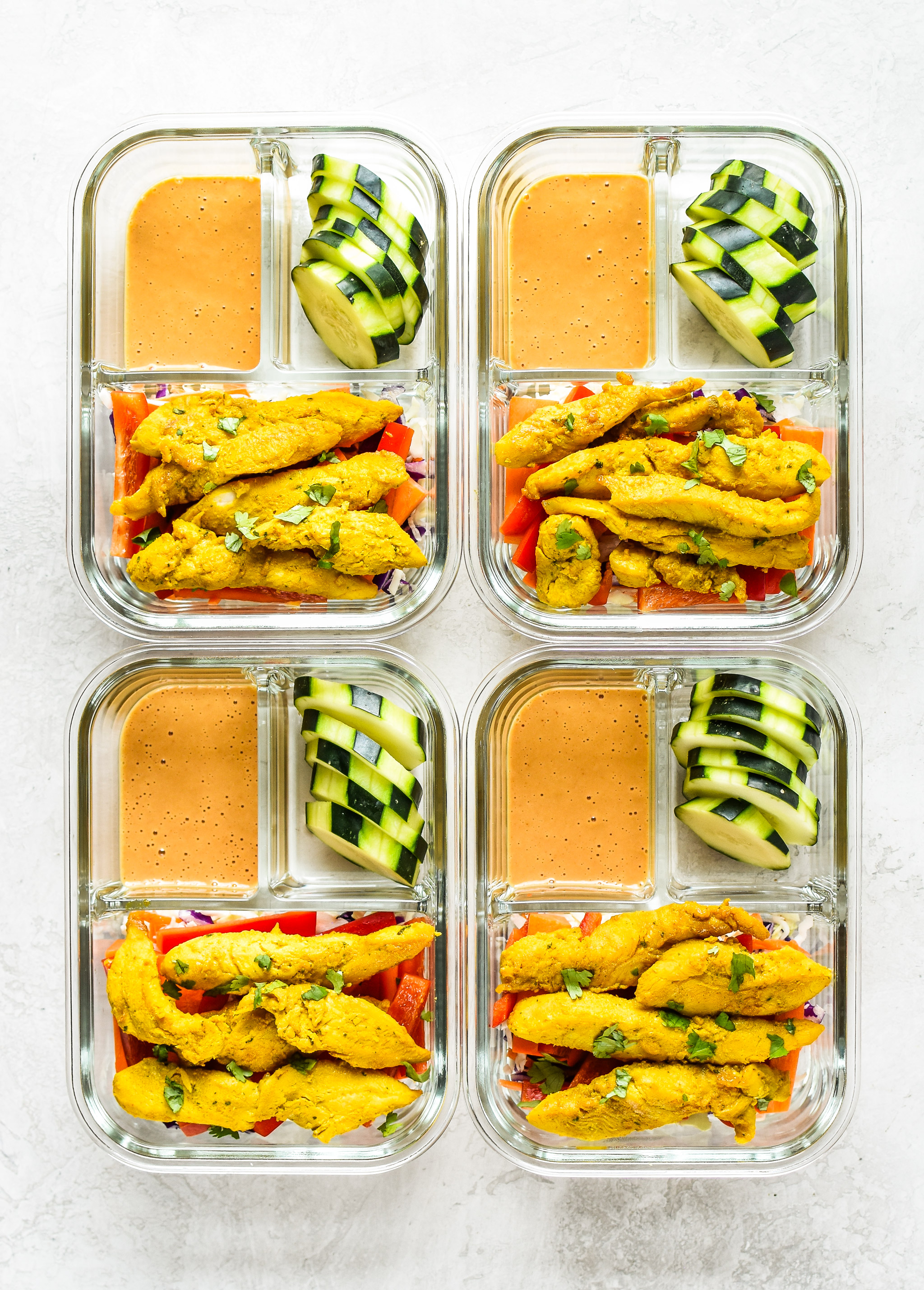 Meal Prep Satay Inspired Thai Chicken Salad Bowls portioned into meal prep containers, viewed from above.