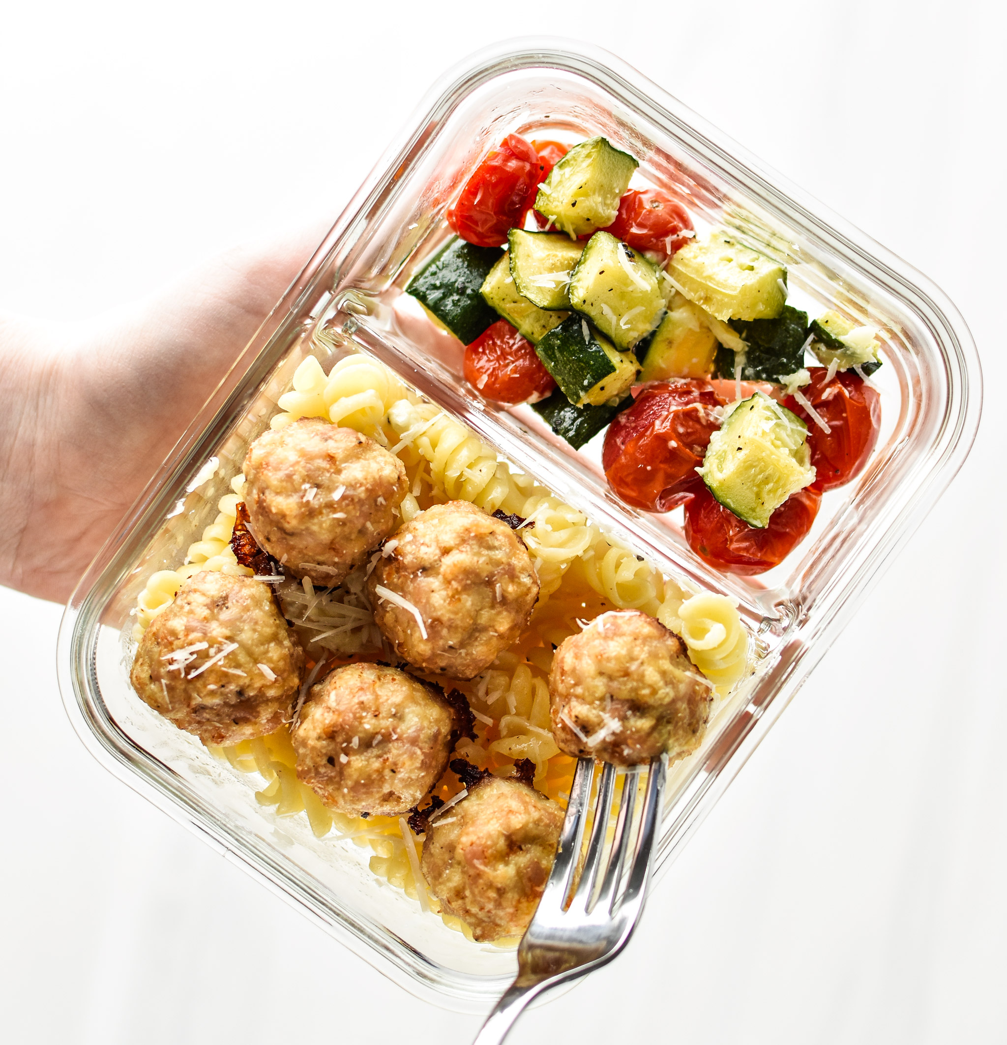 Holding a meal prep bowl from the chicken meatballs two ways meal prep lunches