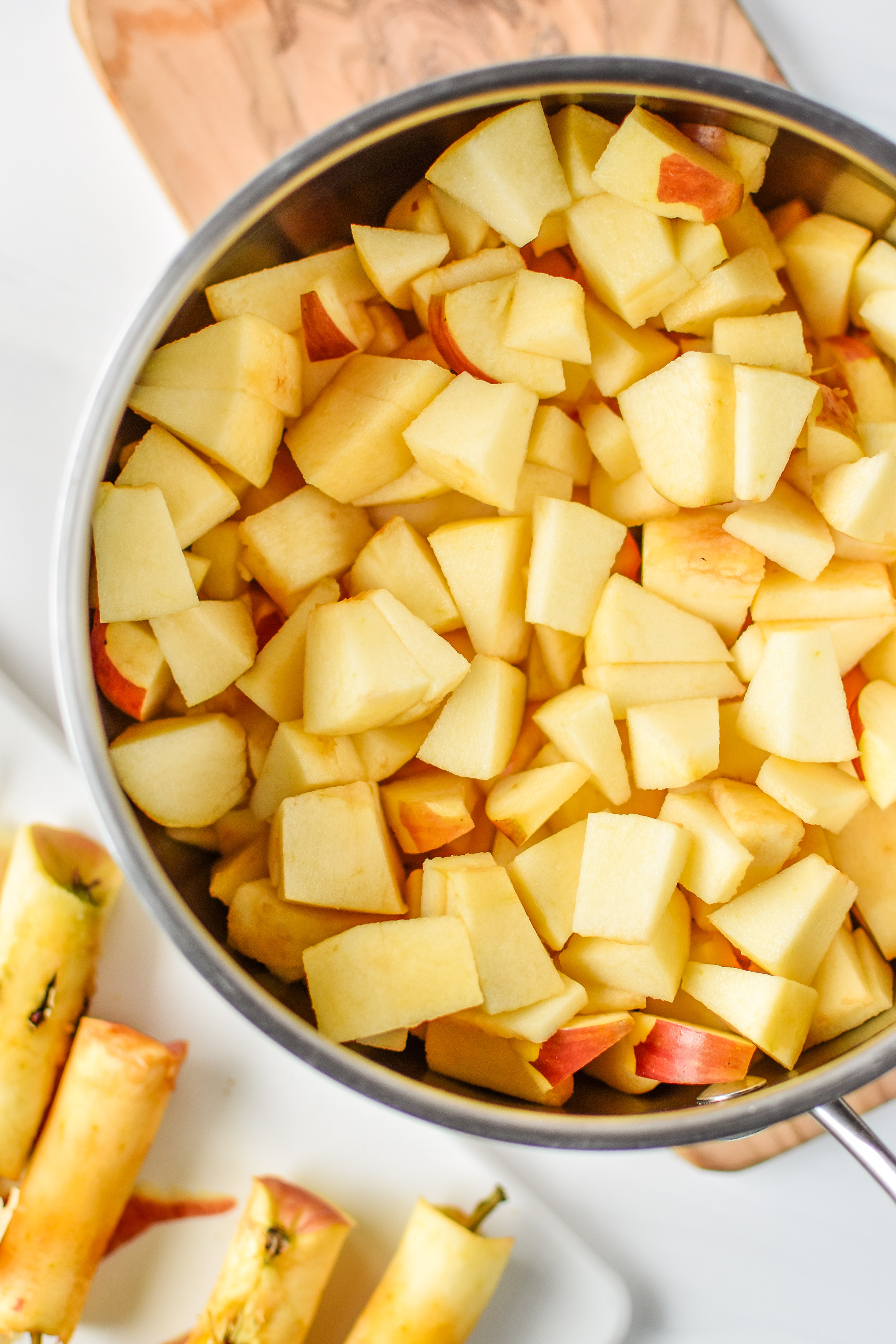 Apples cut and peeled in the pan ready to be cooked down into applesauce. Store bought vs Homemade: Which is Cheaper?