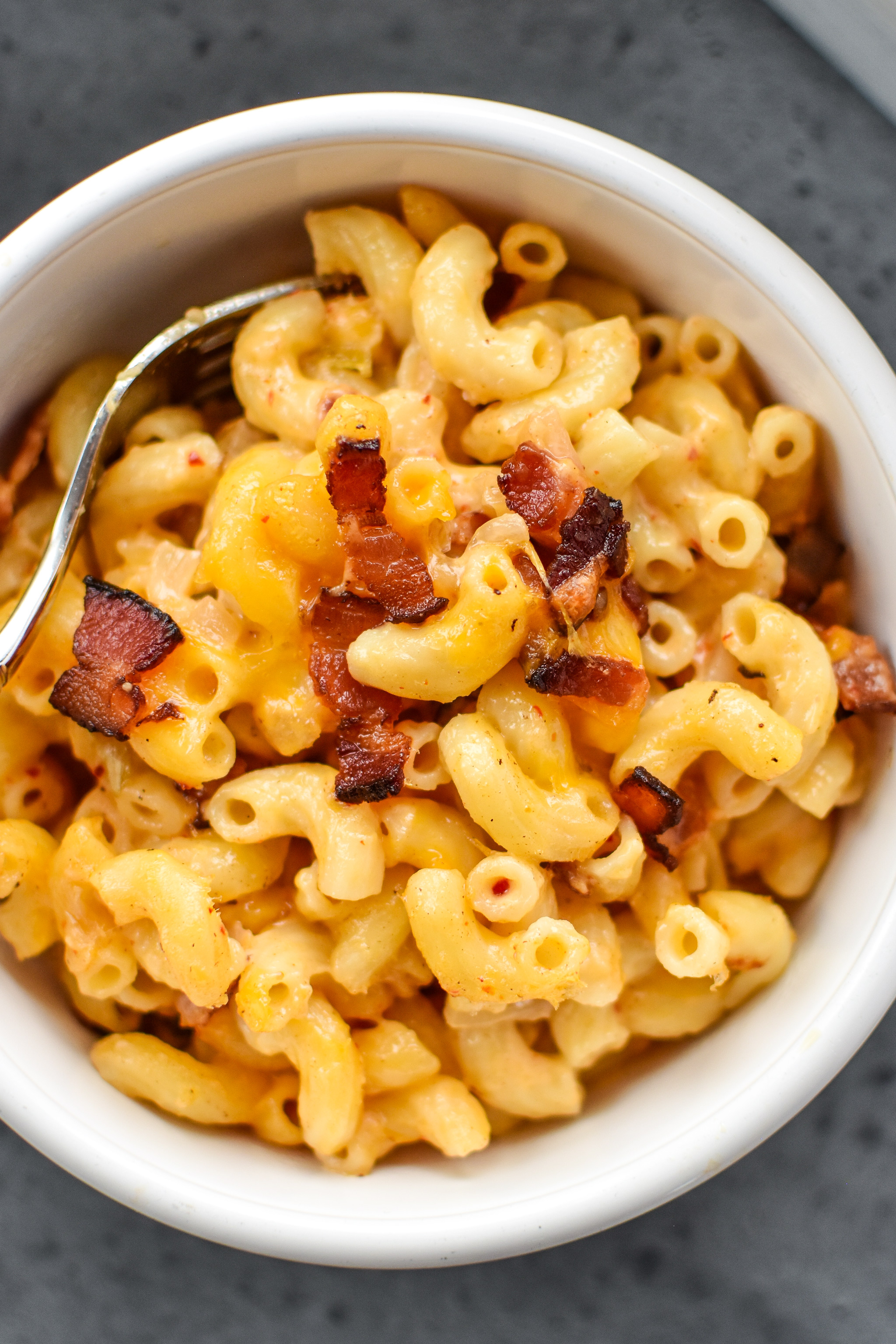 A bowl of kimchi bacon greek yogurt mac and cheese with bacon bits on top.