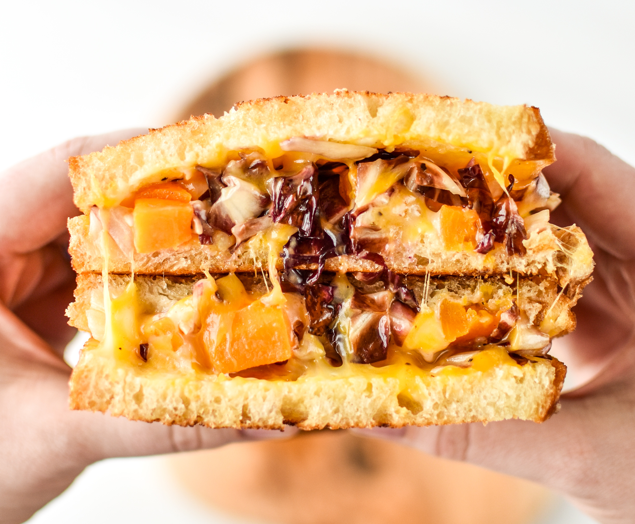 Holding a roasted squash salad grilled cheese sandwich
