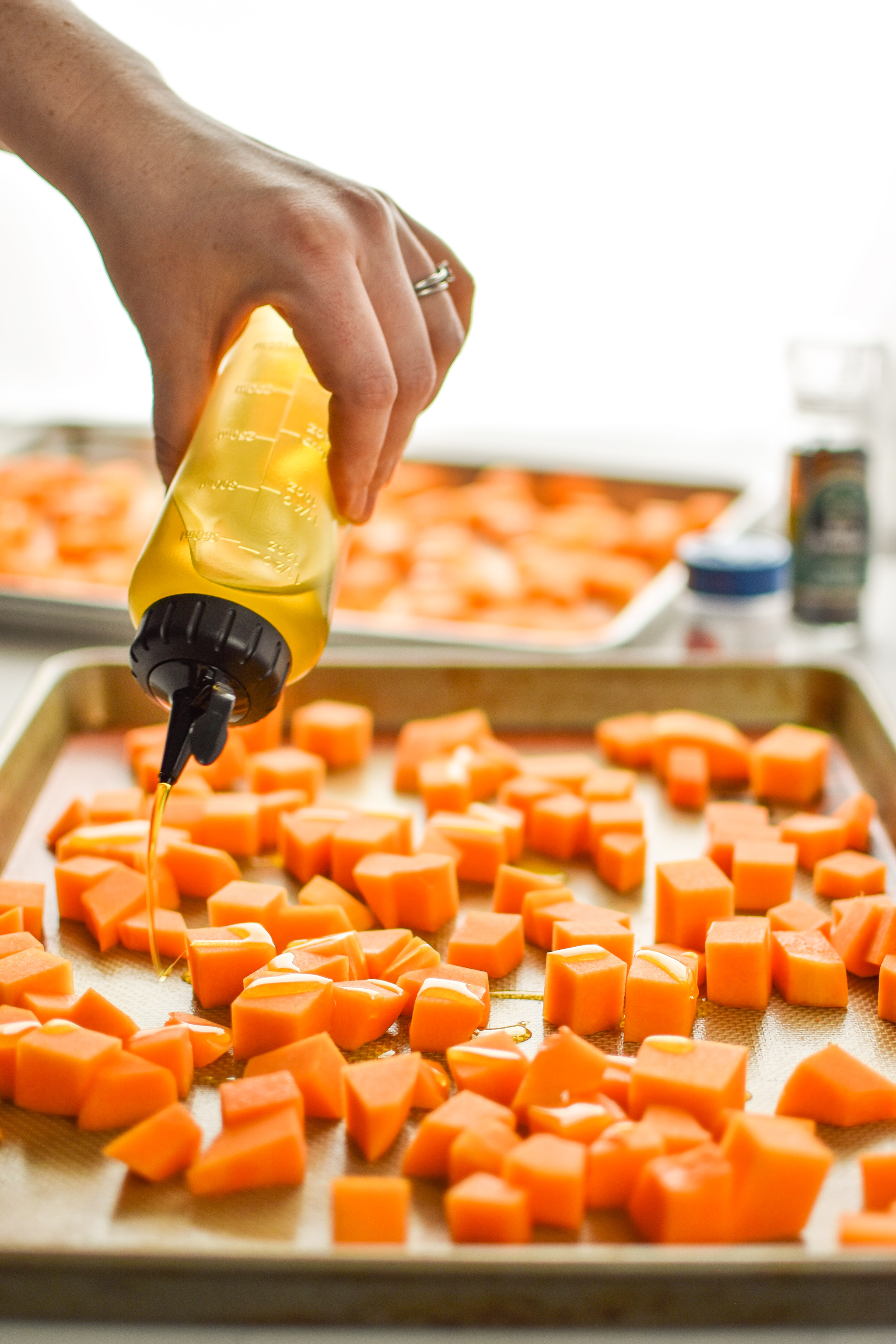 Using a chef squeeze bottle to add oil to the roasted butternut squash