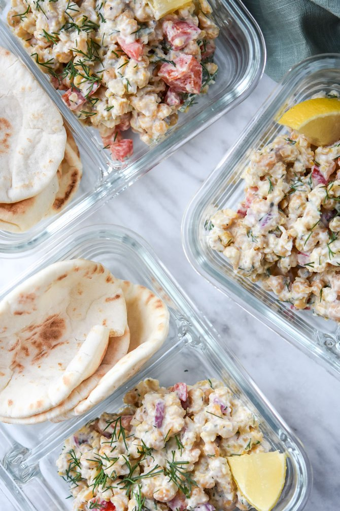 Greek Chickpea salad with pita portioned into glass meal prep container for lunch.