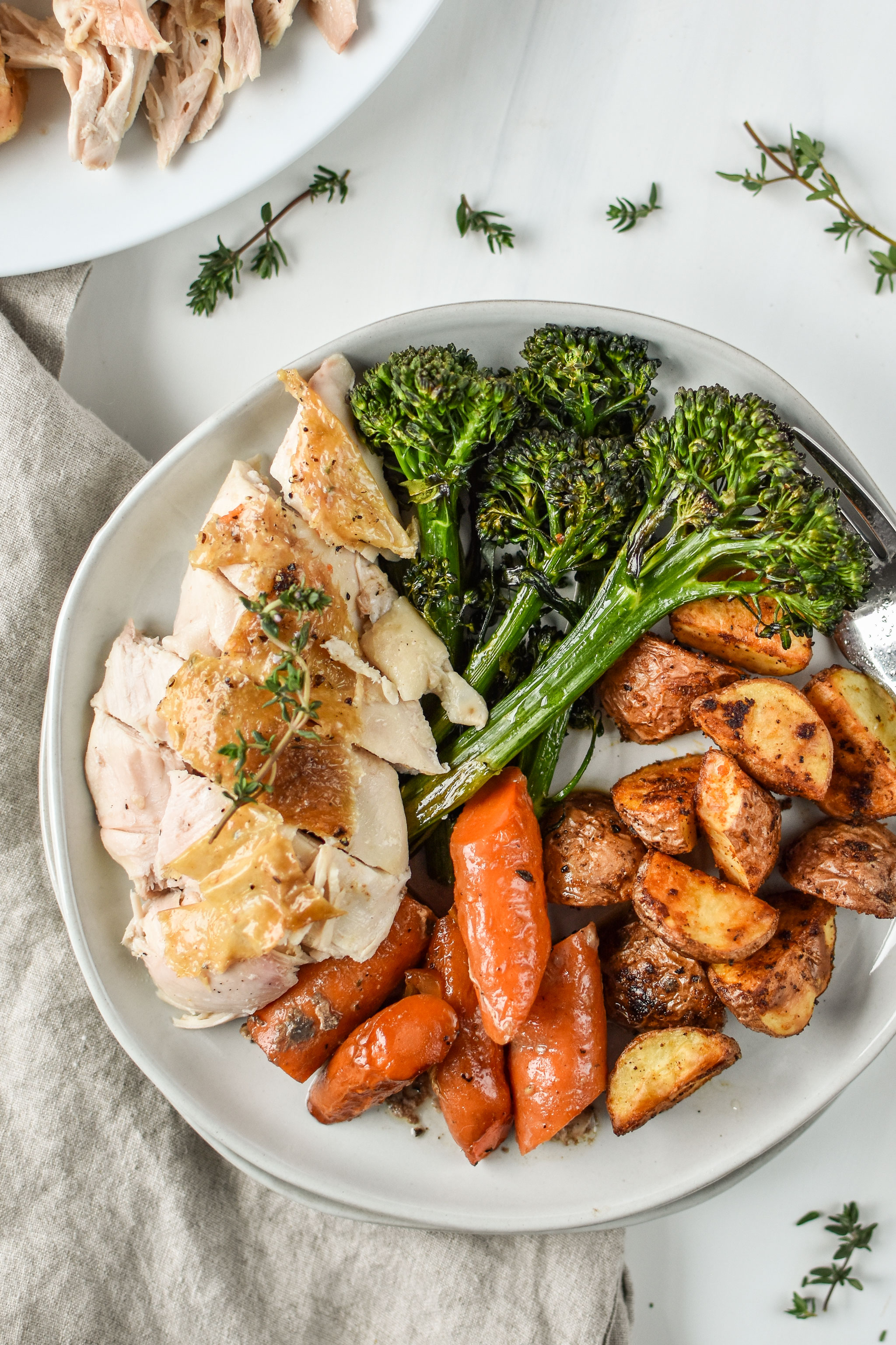 Simple whole roast chicken plated with broccolini, potatoes and carrots, a perfect Whole30 dinner!