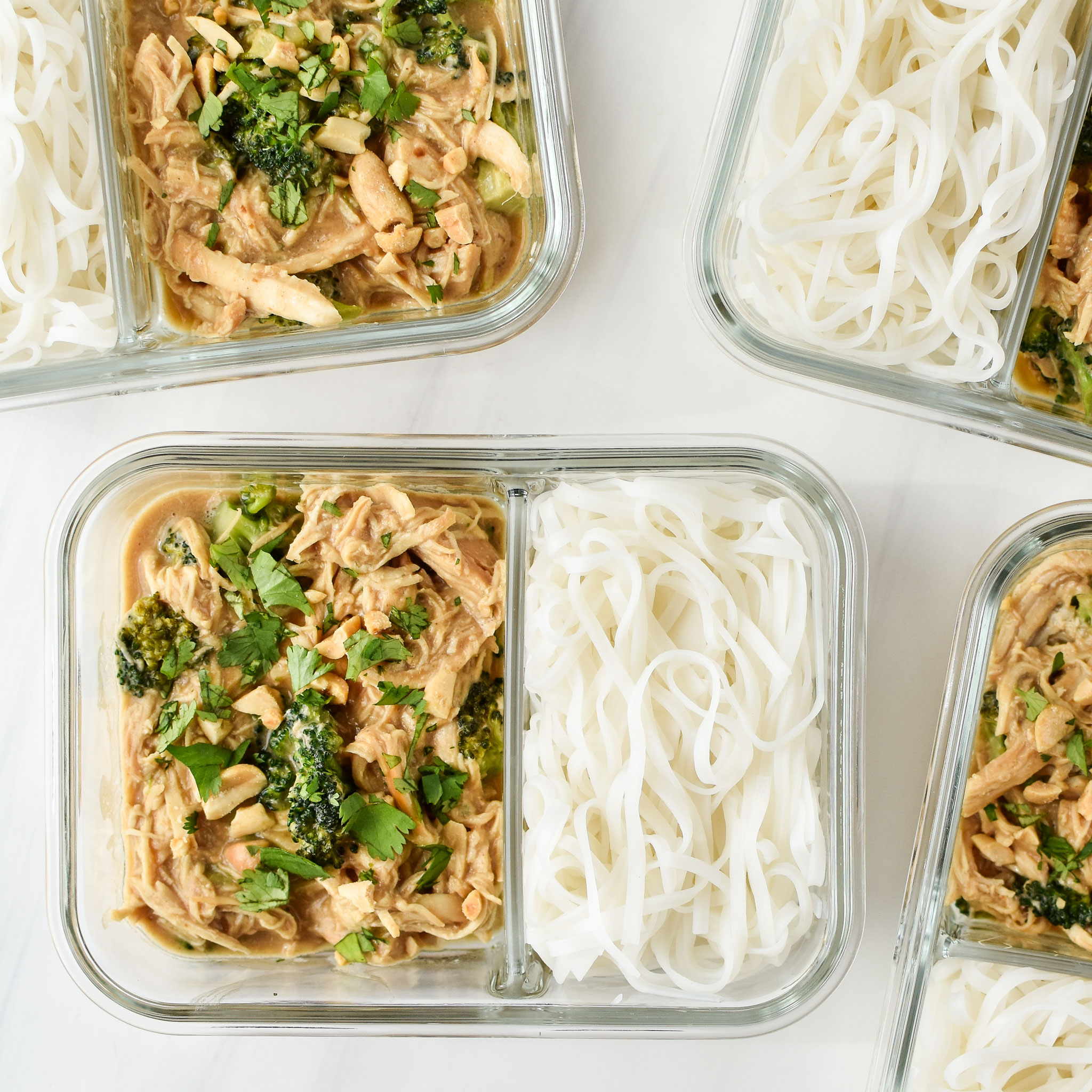 slow cooker peanut chicken noodles meal prep pictured from above in 2 compartment glass meal prep containers