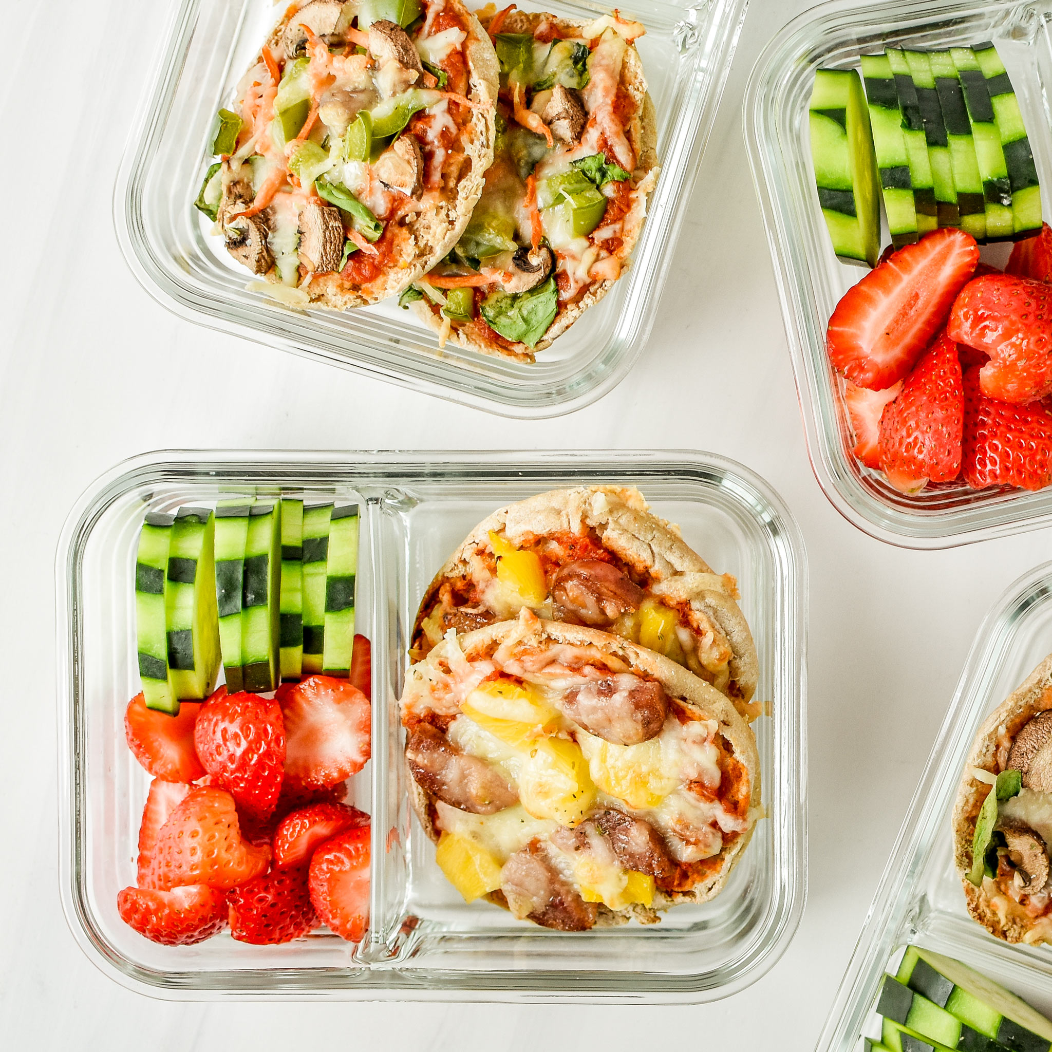English muffin mini pizzas meal prep pictured from above in a meal prep container with fresh fruits and veggies.
