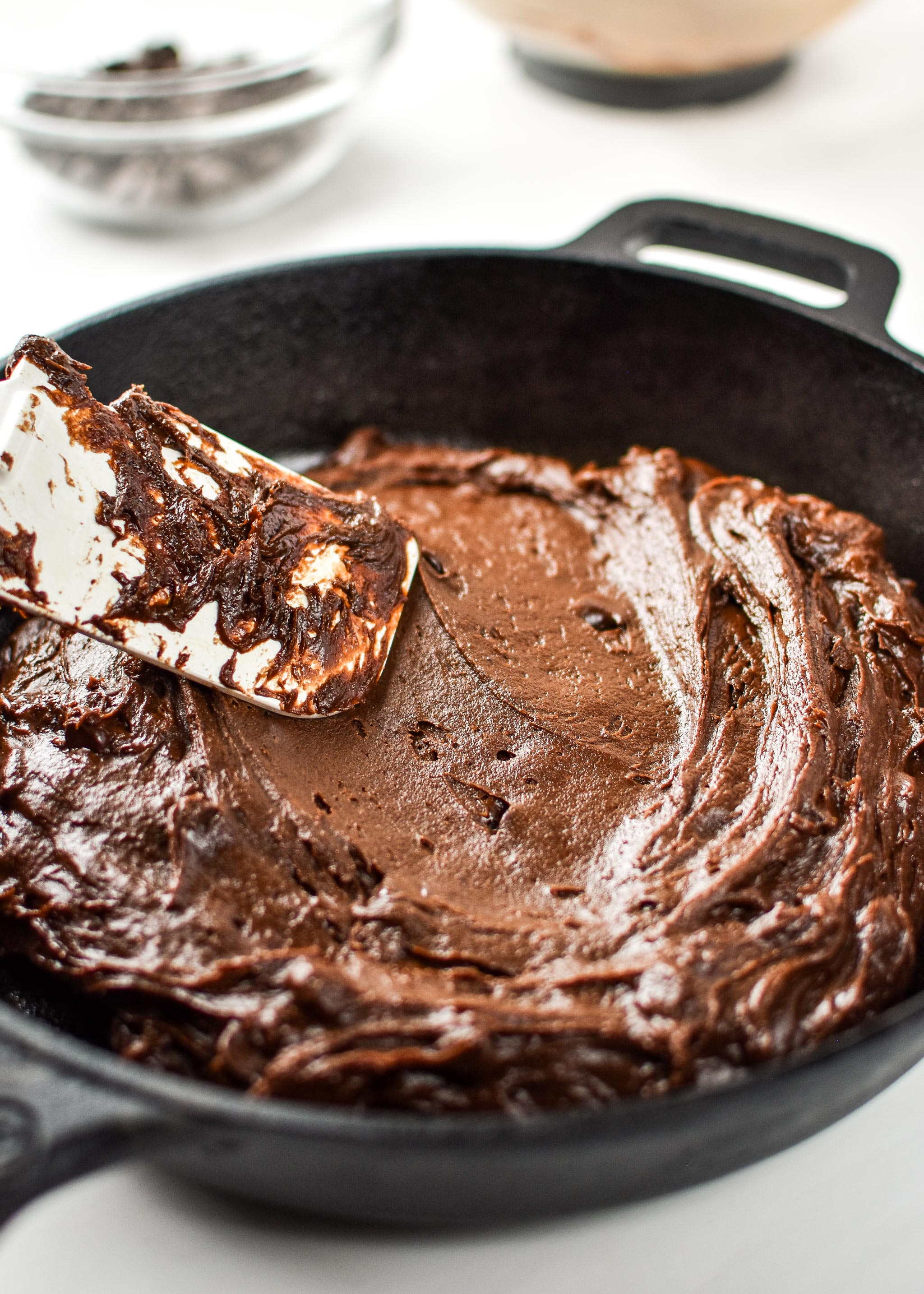 Adding the batter to the cast iron skillet for the sweet potato brownie skillet