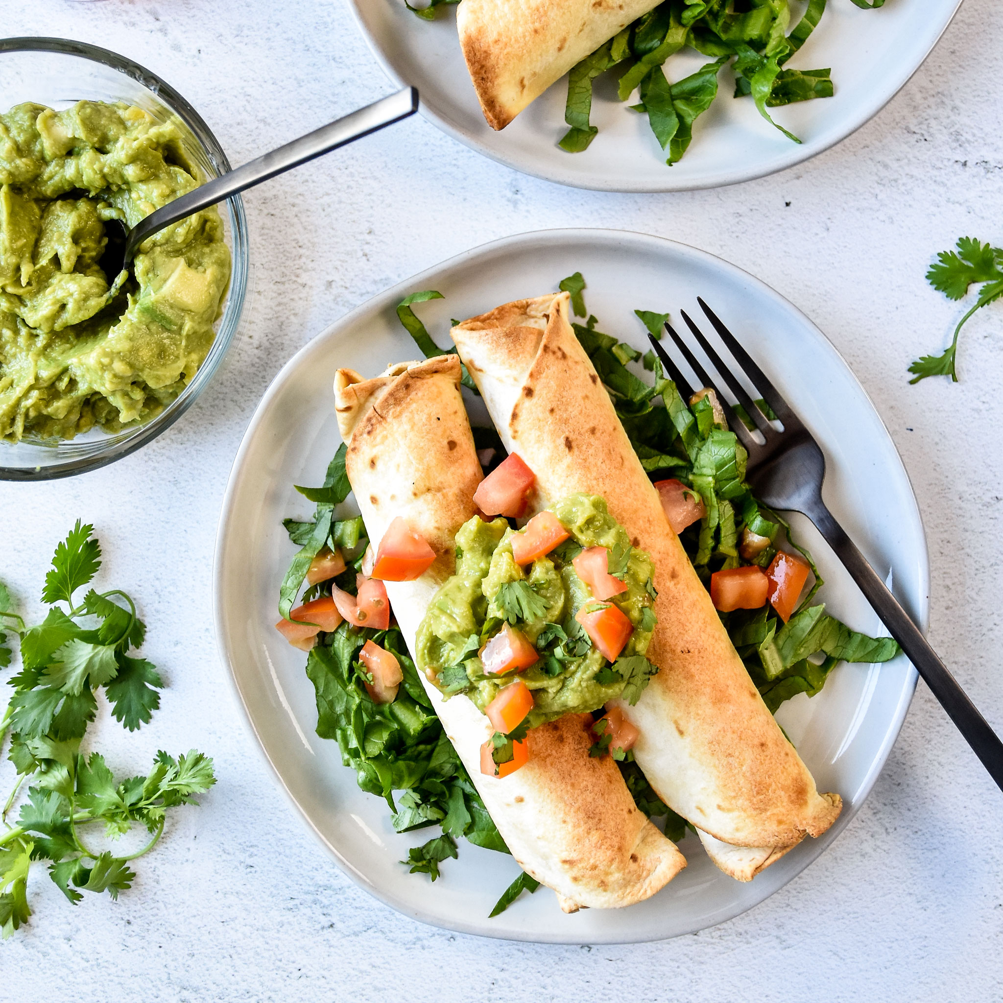 air fryer chicken taquitos made with small flour tortillas and topped with guacamole and tomatoes