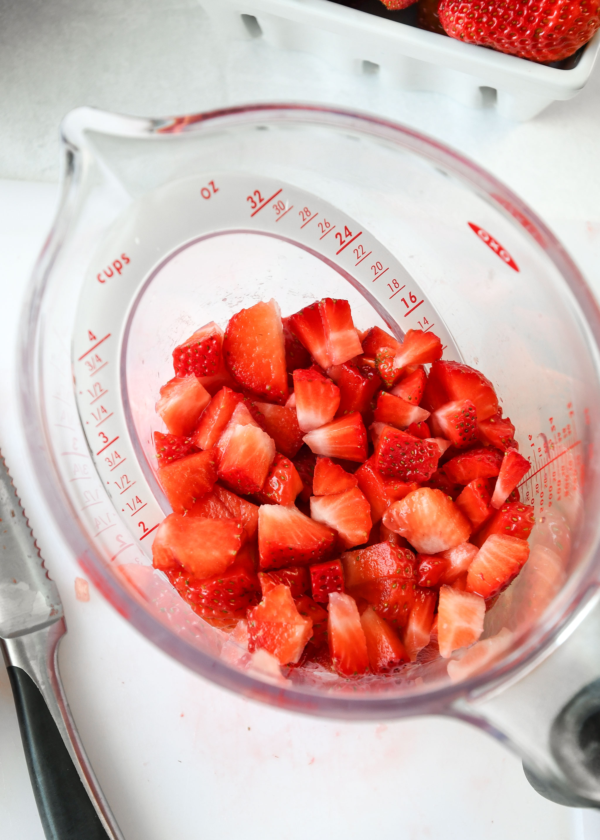 chopped strawberries in a measuring cup for easy strawberry sauce