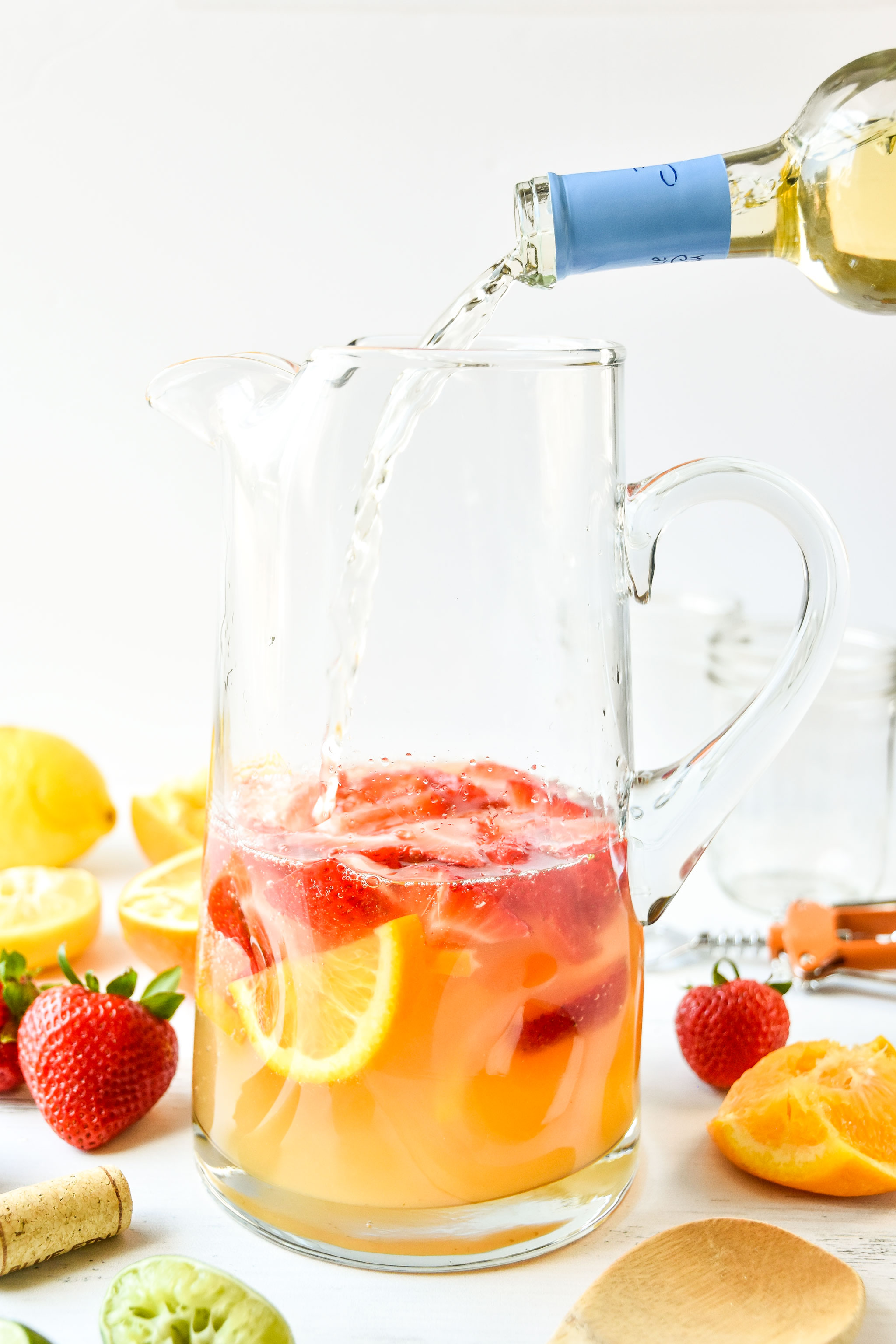 Pouring wine into pitcher of summer white wine sangria