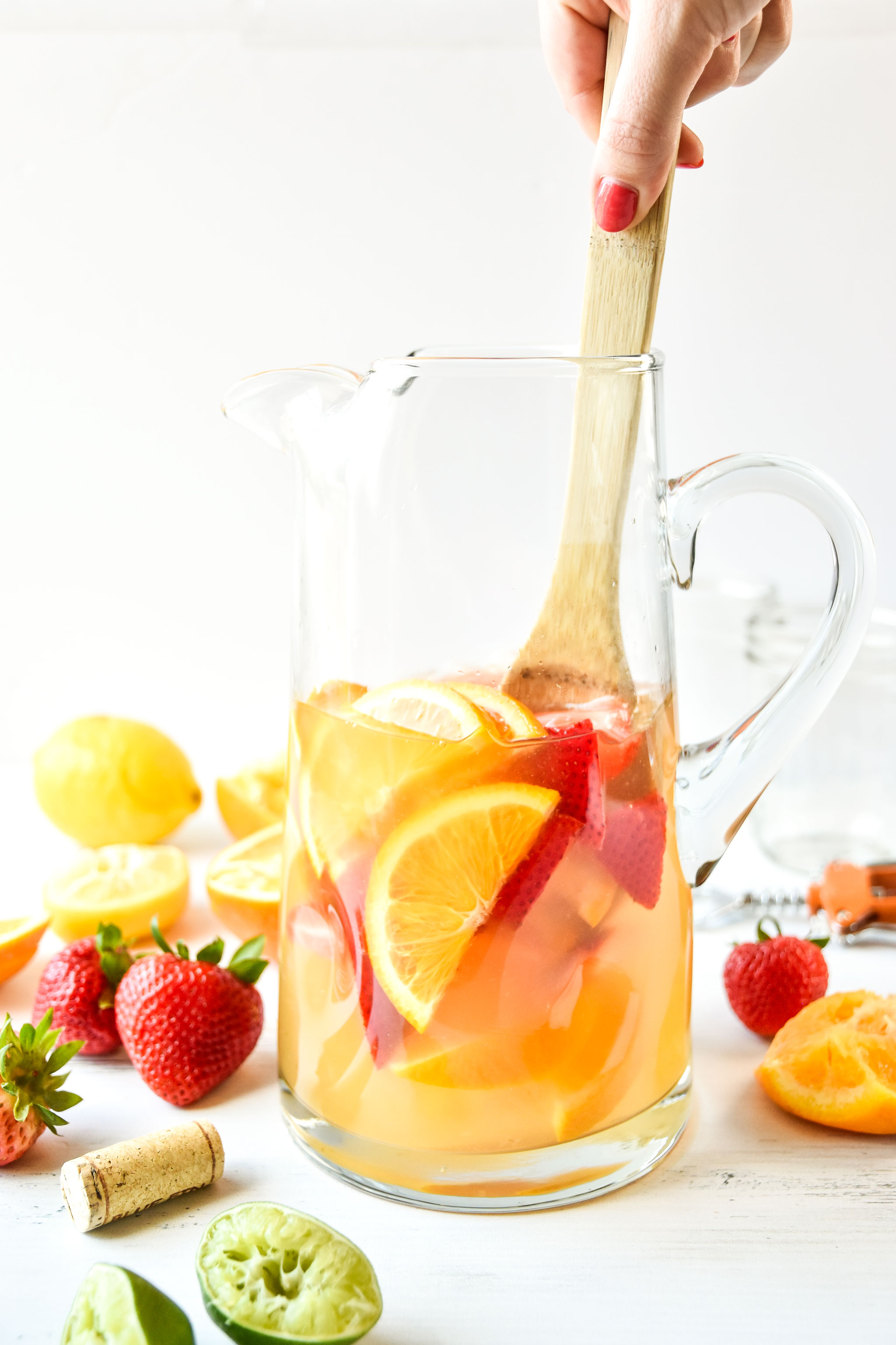 Pitcher of summer white wine sangria being stirred
