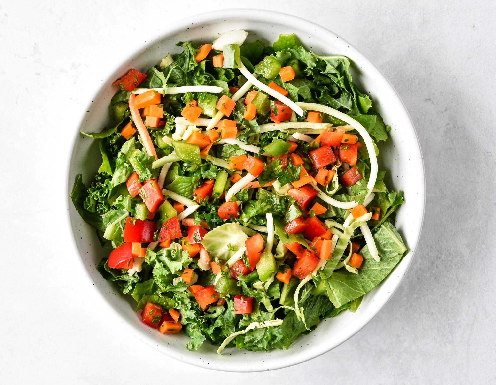 kale salad with vegetable confetti on top