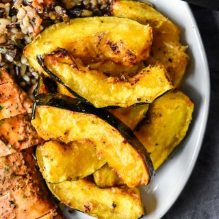 air fryer acorn squash on a plate with rice and chicken