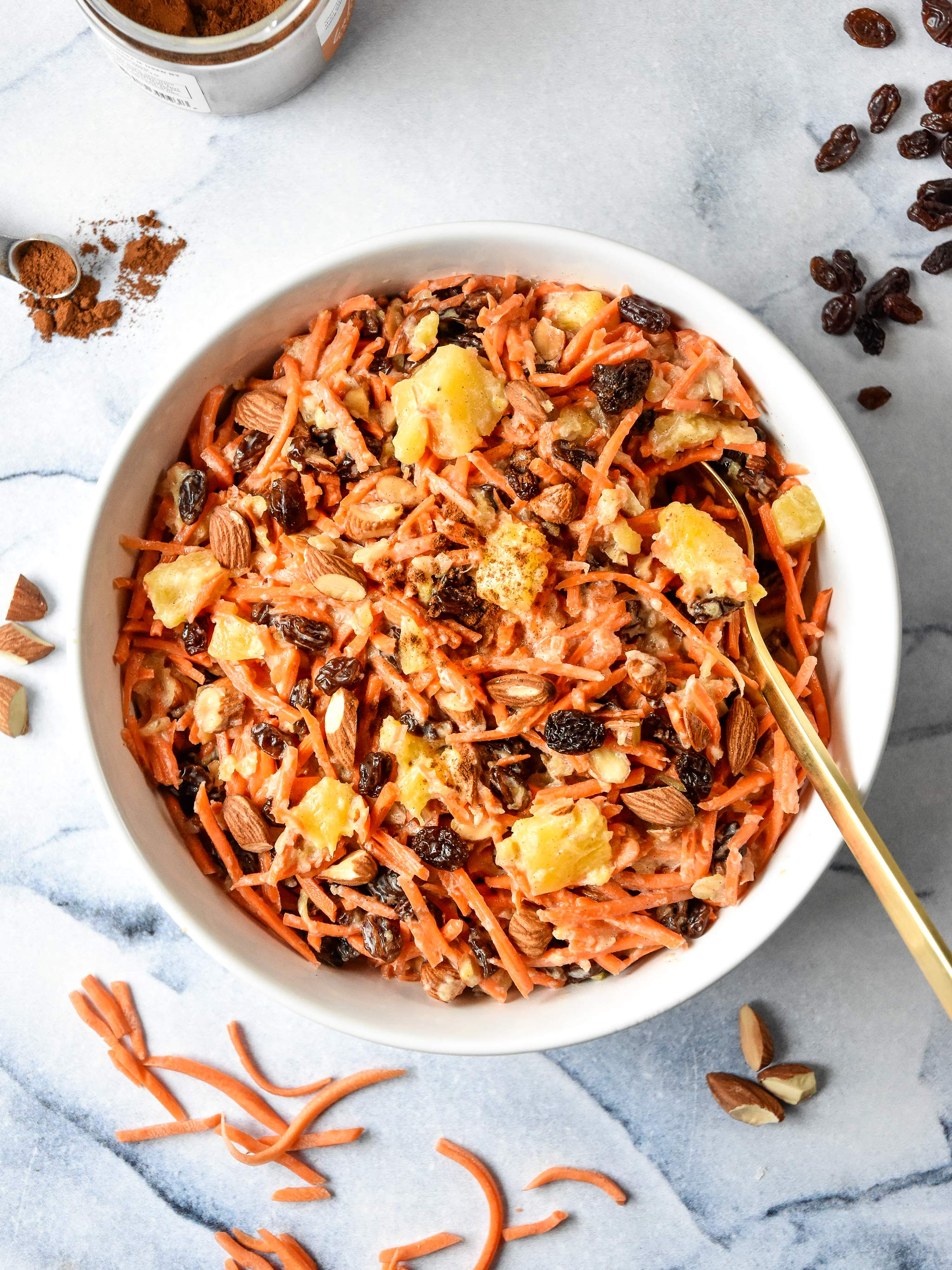 Cinnamon Raisin Carrot Salad in a bowl with a gold spoon