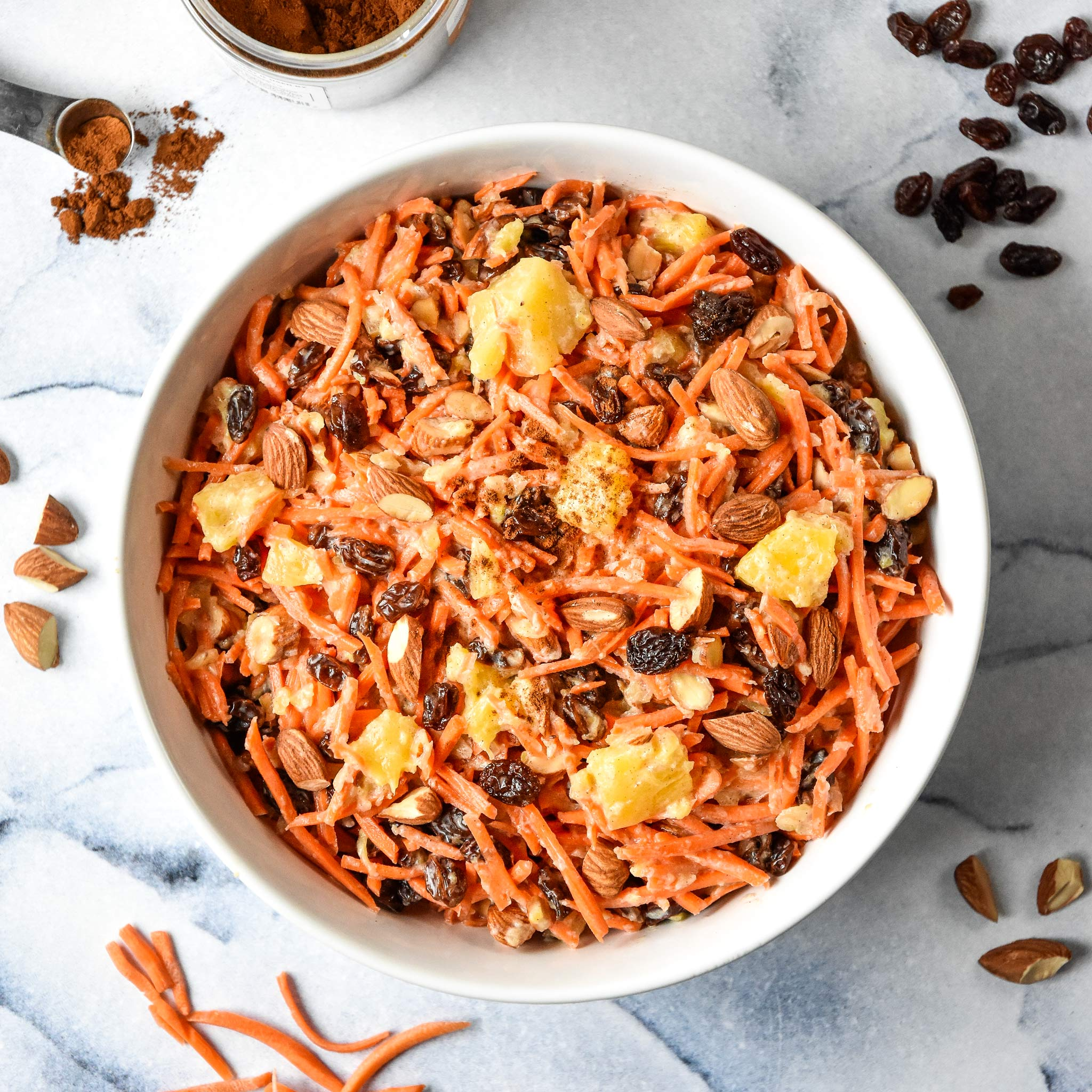 cinnamon raisin carrot salad in a white bowl from the top