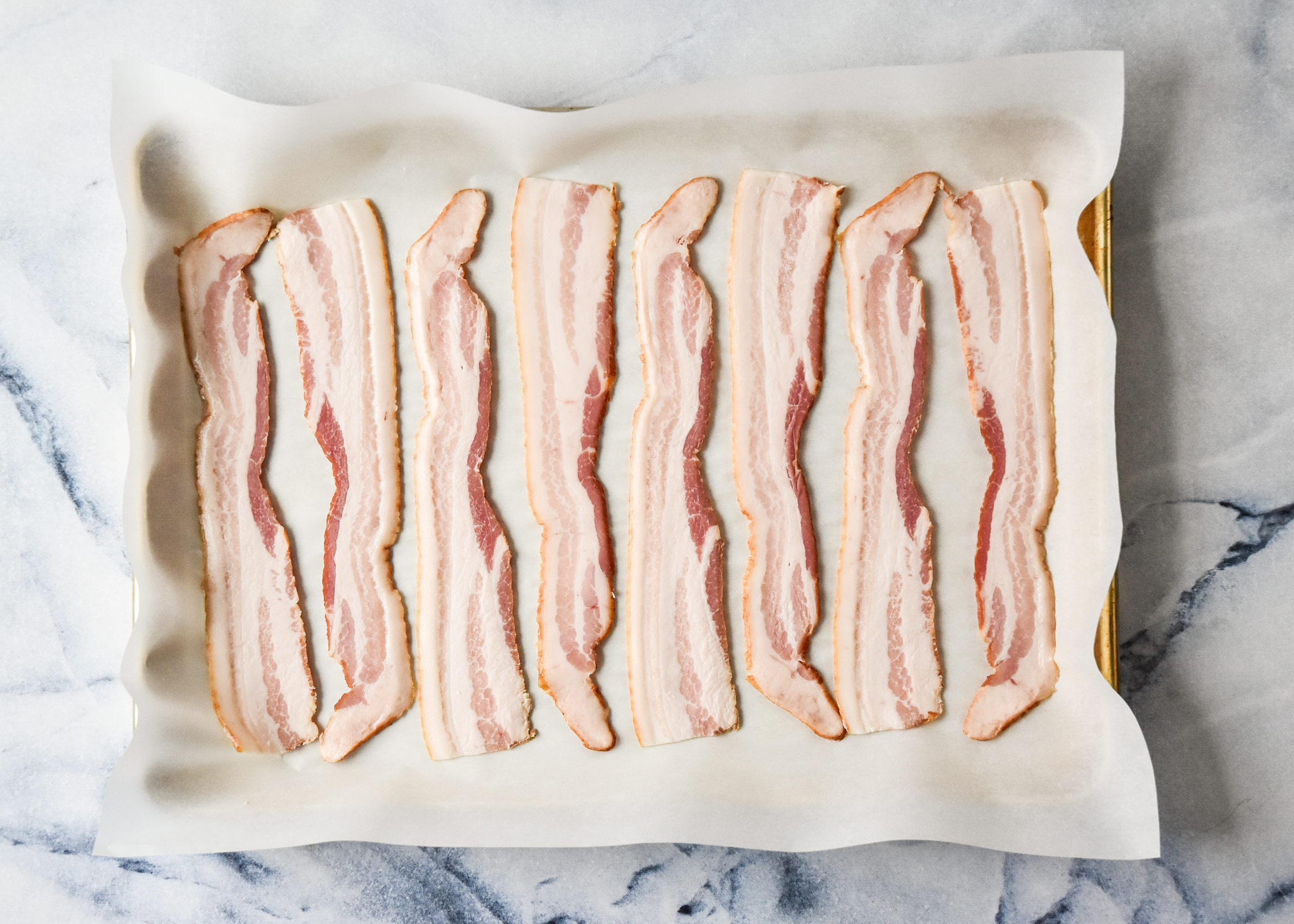 raw bacon strips on a baking sheet