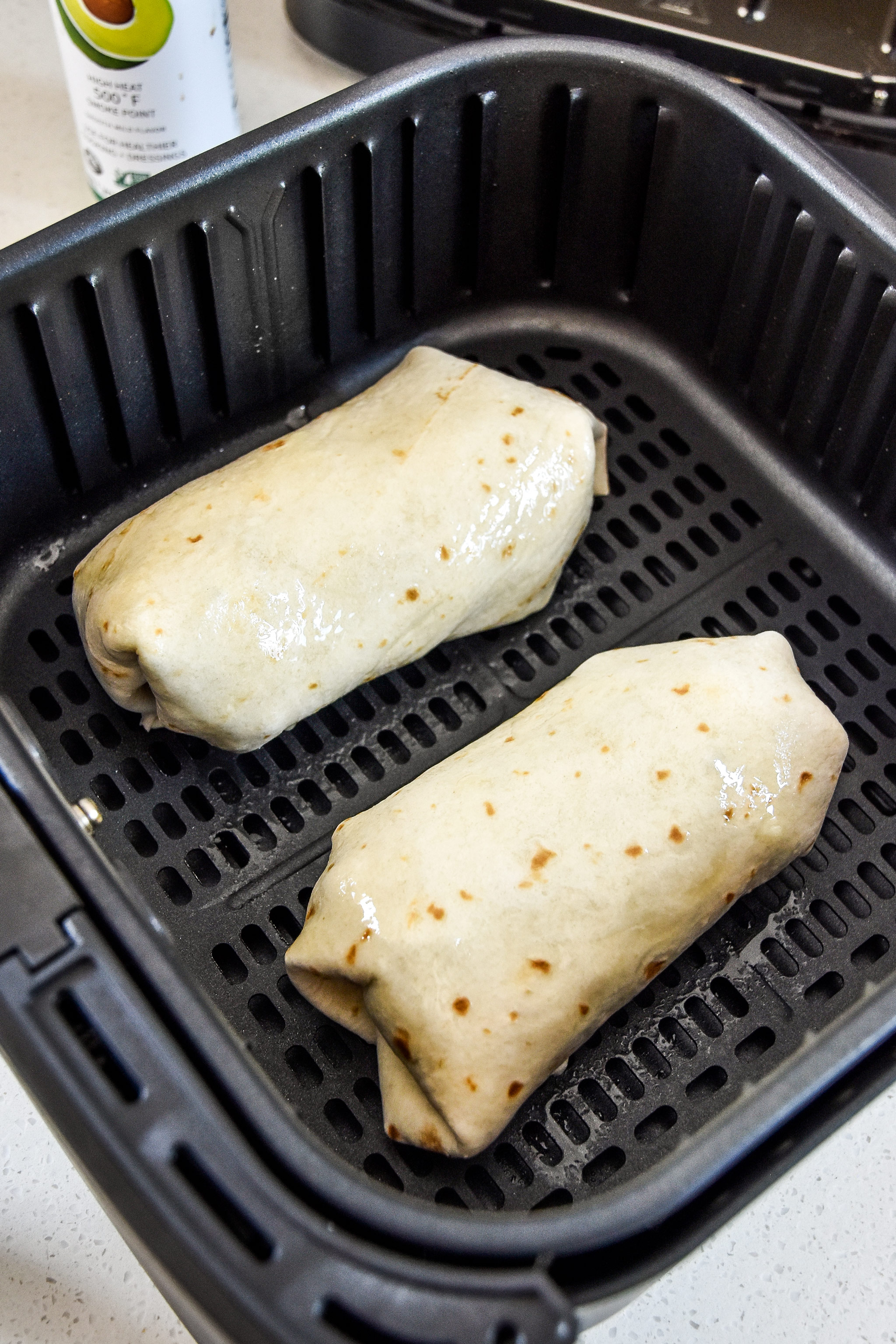 wrapped burritos about to be cooked in the air fryer