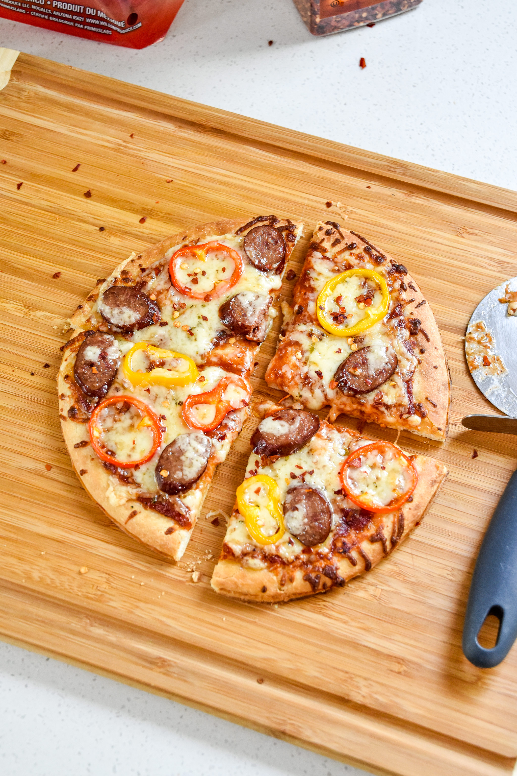 sausage and pepper personal pizza fresh from the oven cut with a pizza cutter