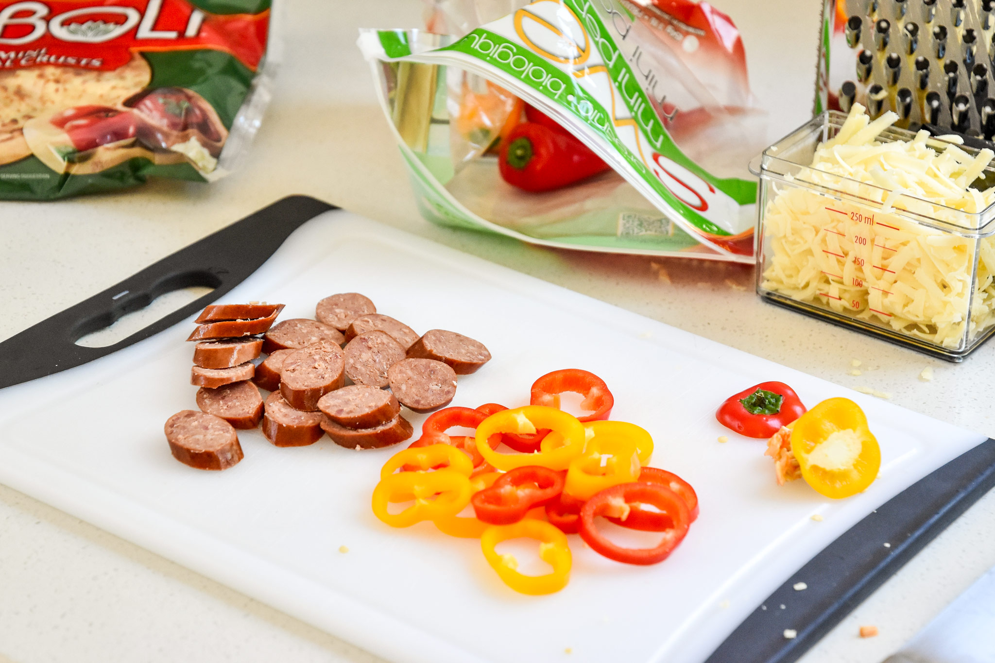 Ingredients for the sausage and pepper personal pizzas being cut on a cutting board