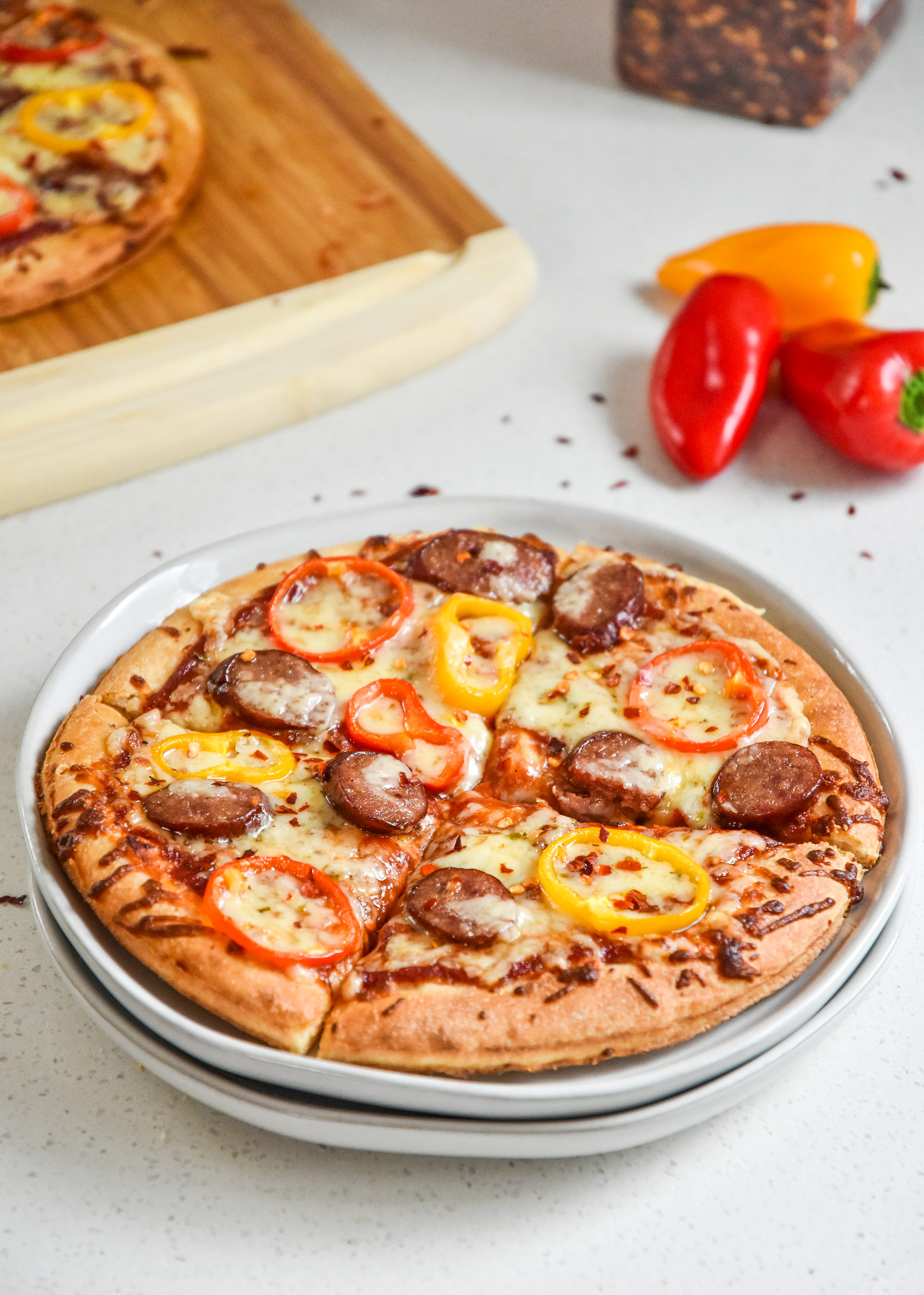 sausage and pepper personal pizzas served on a plate